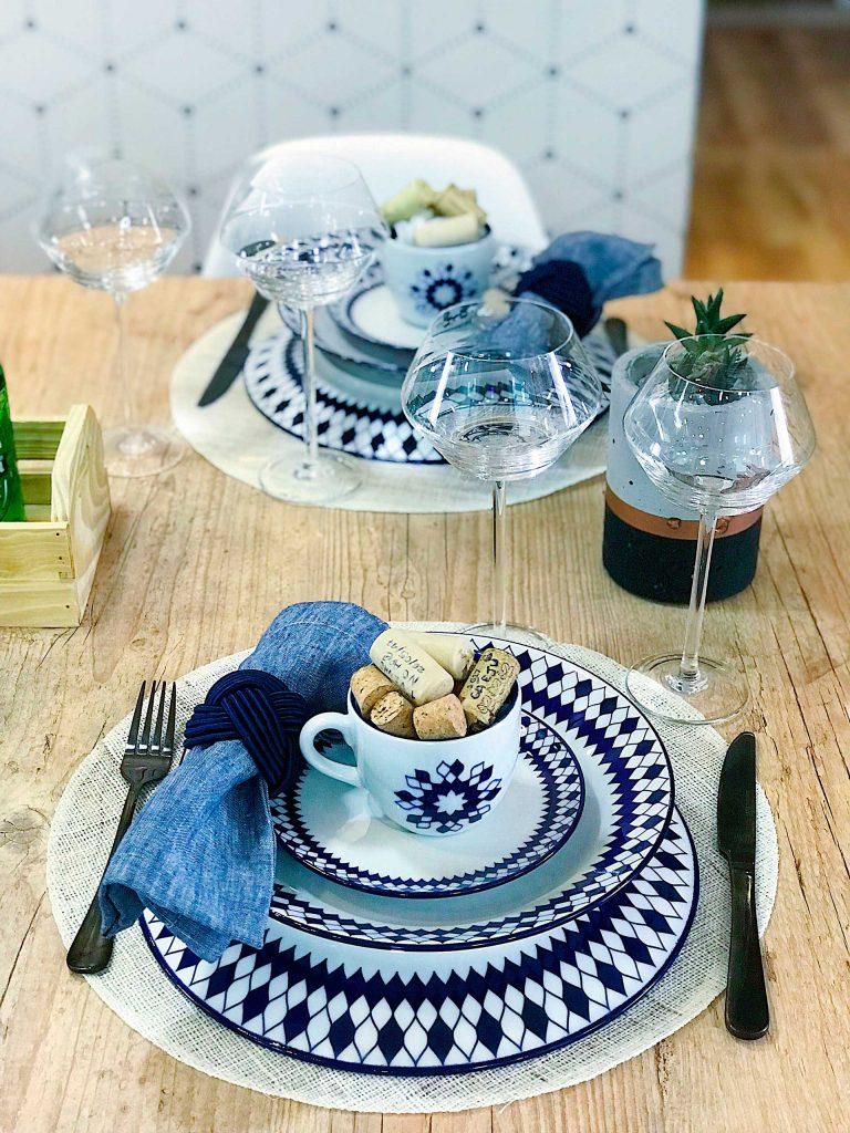 Imagem: Detalhes da mesa para o Dia dos Pais produzida pelo casal que comanda o blog Meu Apê 34. O guardanapo em tom de azul conversa com a cor da decoração da louça, enquanto os talheres na cor preta criam um contraste interessante.