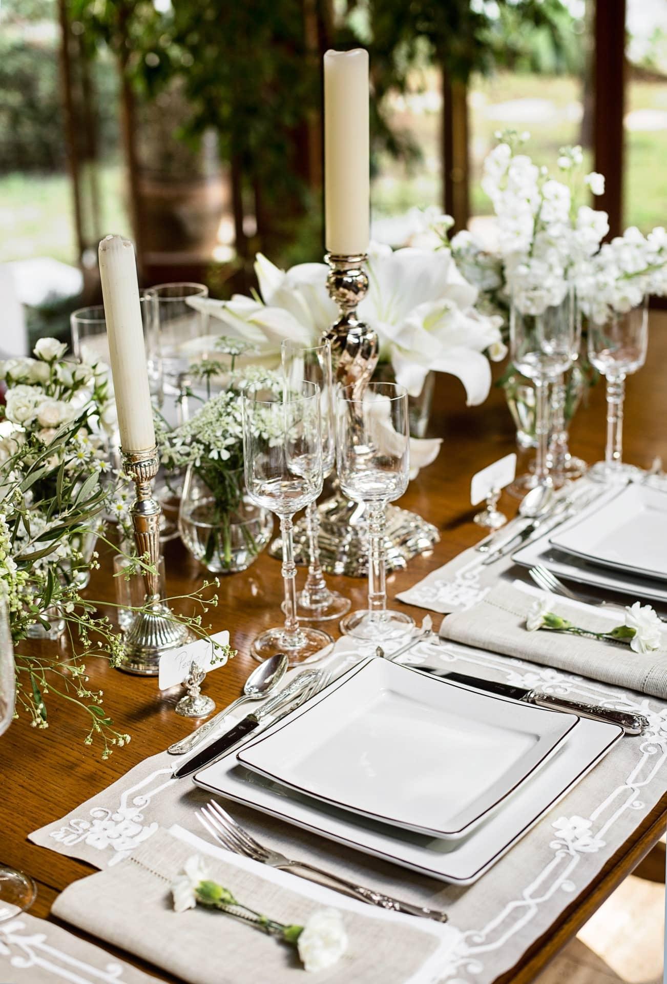 Imagem: Glamour à prova de erro: castiçais de prata, com velas brancas, ficam em meio a pequenos arranjos de flores, também brancas.Foto: Elisa Correa.