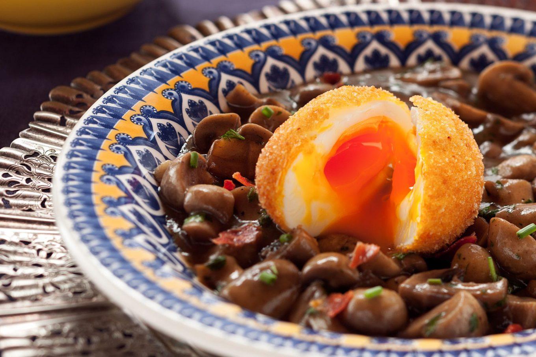 Imagem: Ovo mollet empanado servido com um mix de cogumelos. Receita do restaurante Le Jazz Brasserie. Foto: Raphael Günther/Bespoke Content.