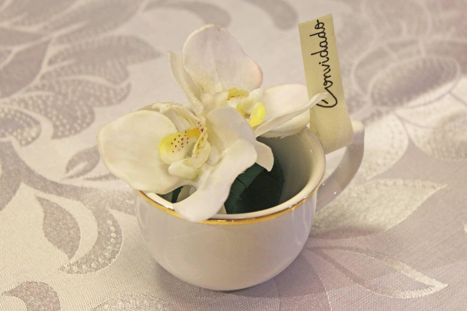 Imagem: Na xícara da linha Flamingo Sofia, da Oxford, o marcador de lugar é fixado à asa. Para enfeitar, coloque uma orquídea branca.