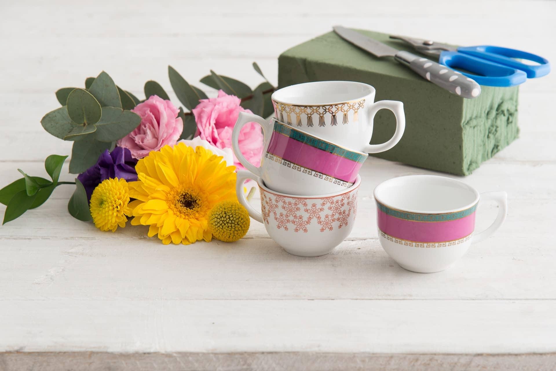 Imagem: Passo 1: Reúna todo o material necessário para o arranjo floral. Escolhemos duas xícaras da linha Flamingo Joia Brasileira, uma da linha Flamingo Macramê (com laços em ouro) e outra da linha Flamingo Dama de Honra (com desenho rendado), tudo da Oxford Porcelanas. Foto: Cacá Bratke.