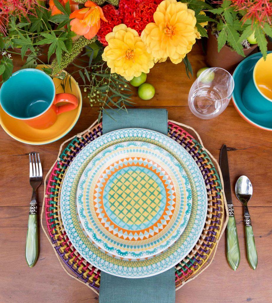 Imagem: Os pratos são da coleção Floreal Bilro, da Oxford Daily. A inspiração dessa decoração vem das rendas artesanais de bilro, como o próprio nome sugere. Aqui eles foram combinados com um sousplat com esse mesmo estilo. O guardanapo e os talheres trazem as mesmas cores presentes na decoração da louça. Foto: Julia Ribeiro.