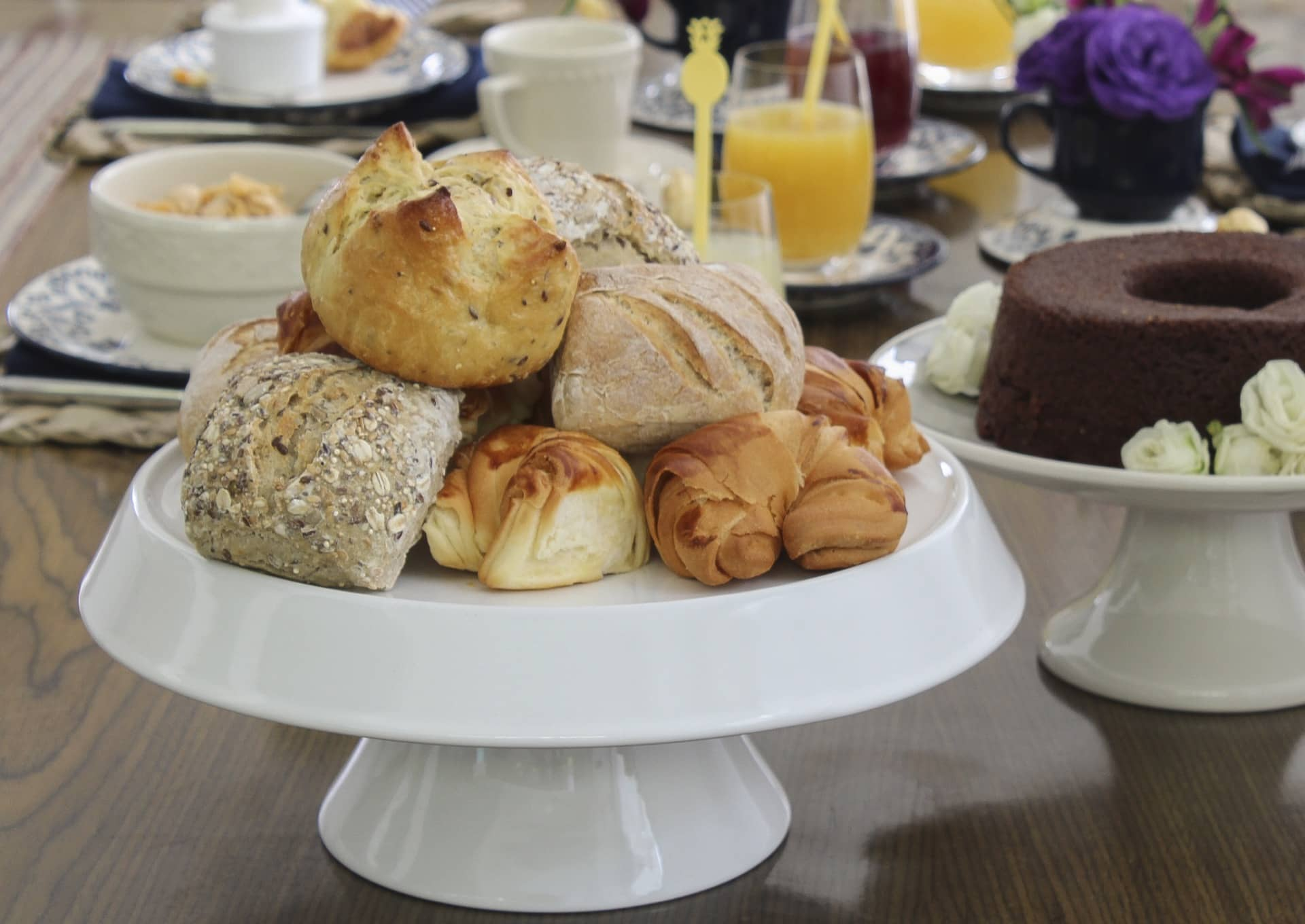 Imagem: No lugar de uma cesta de pães, use um prato de bolo para dar altura. Empilhados, os pãezinhos de diferentes formatos ficam com cara de festa. Prato de bolo Tower da Oxford Porcelanas. Foto: Cacá Bratke