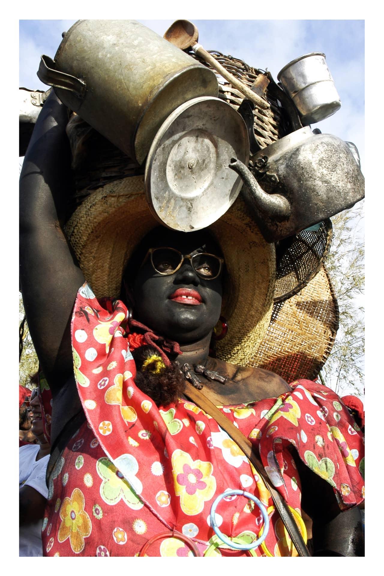Imagem: Na Festa dos Lambe-Sujos e Caboclinhos, Mãe Suzana é a matriarca que alimenta os negros. Por isso, carrega na cabeça utensílios de todo tipo. Foto: Lucio Telles.