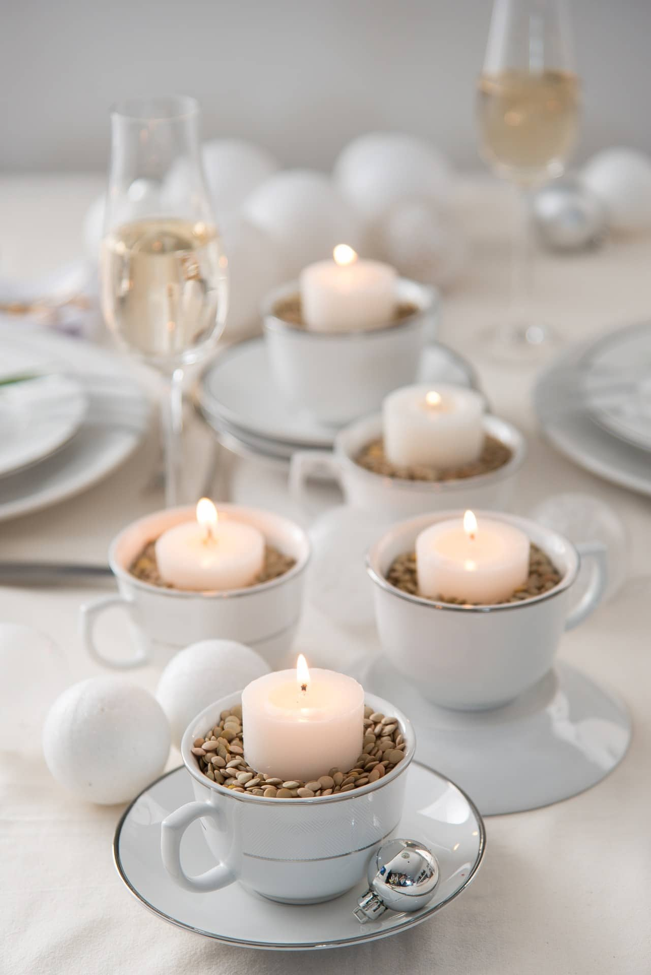 Imagem: Para iluminar a noite, xícaras com lentilha servem de base para as velas. Varie a altura do conjunto virando alguns pires de cabeça para baixo, e empilhando dois ou três pratinhos. Xícaras da coleção Flamingo Diamond da Oxford Porcelanas. Foto: Cacá Bratke.