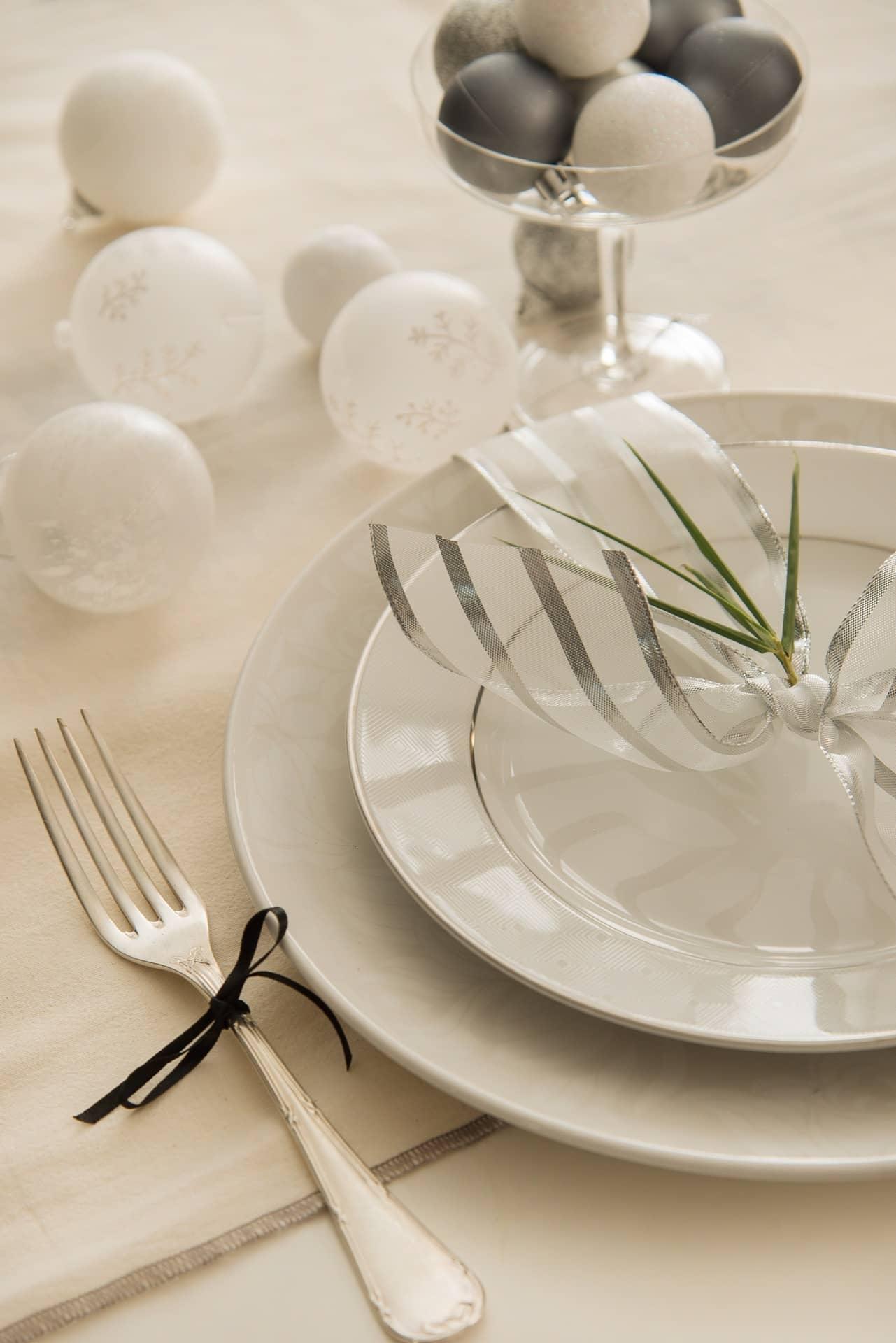 Imagem: Até o garfo vem com roupa de festa: um laço de fita bem fininha. Algumas bolas natalinas ficam soltas sobre a mesa, para dar um ar descontraído. Foto: Cacá Bratke.