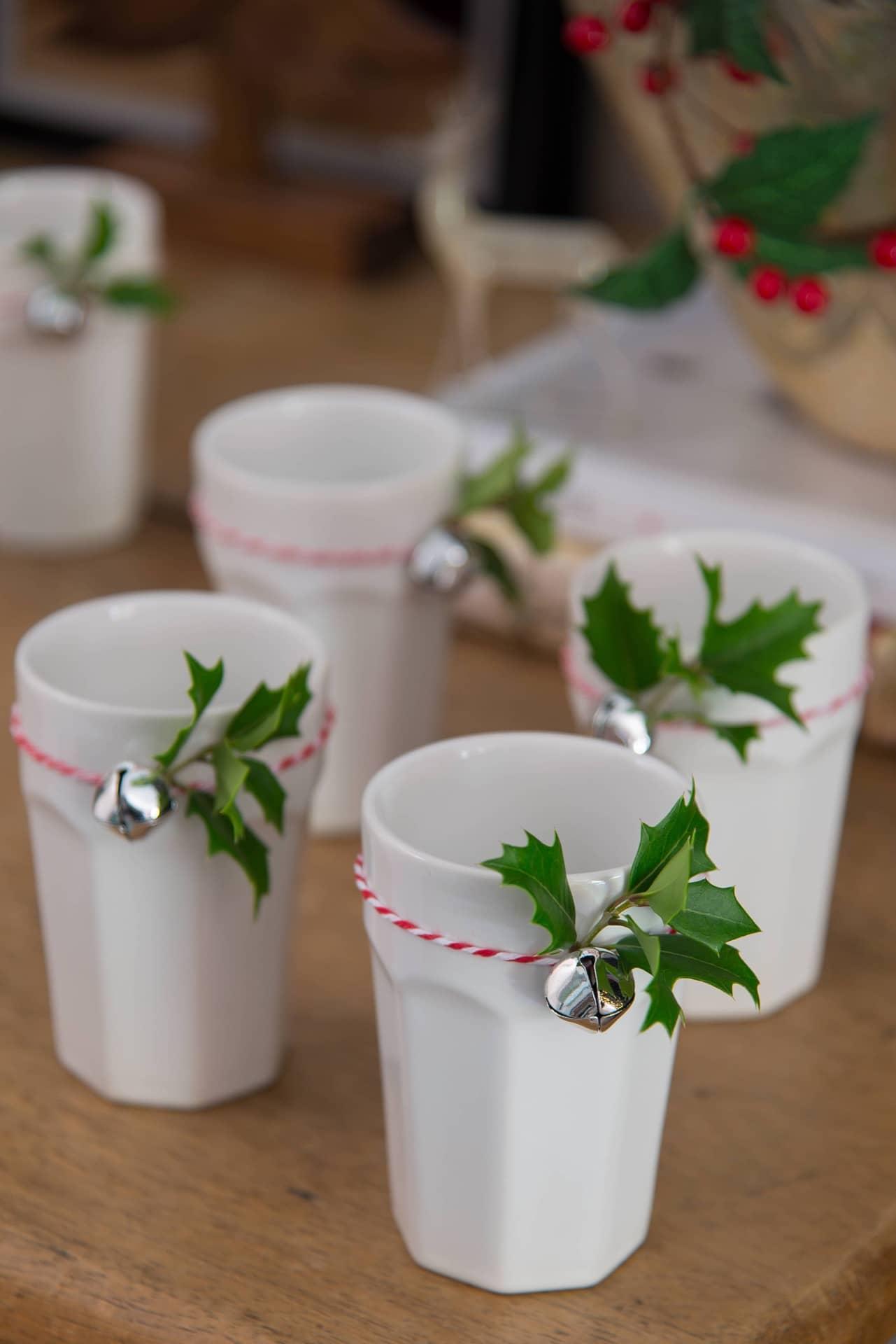 Imagem: Os copos de cerâmica ganham enfeites feitos com barbante bicolor, guizos e folhas de azevinho natural. Eles podem ficar num aparador ou mesinha lateral. Foto: Cacá Bratke.