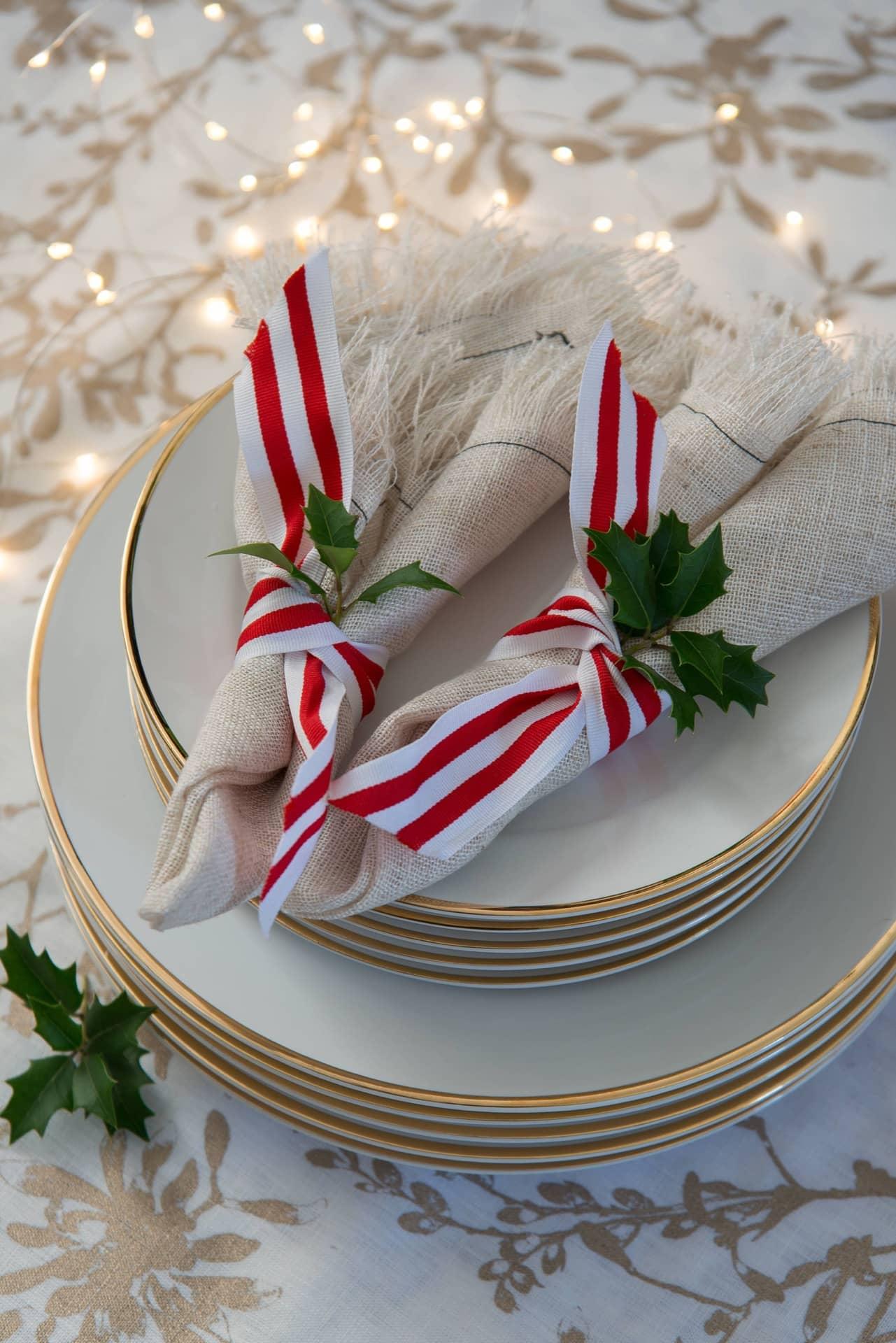 Imagem: Na mesa de Natal decorada, até os guardanapos de linho da @carolroverem ganham fitas e azevinhos.Foto: Cacá Bratke.
