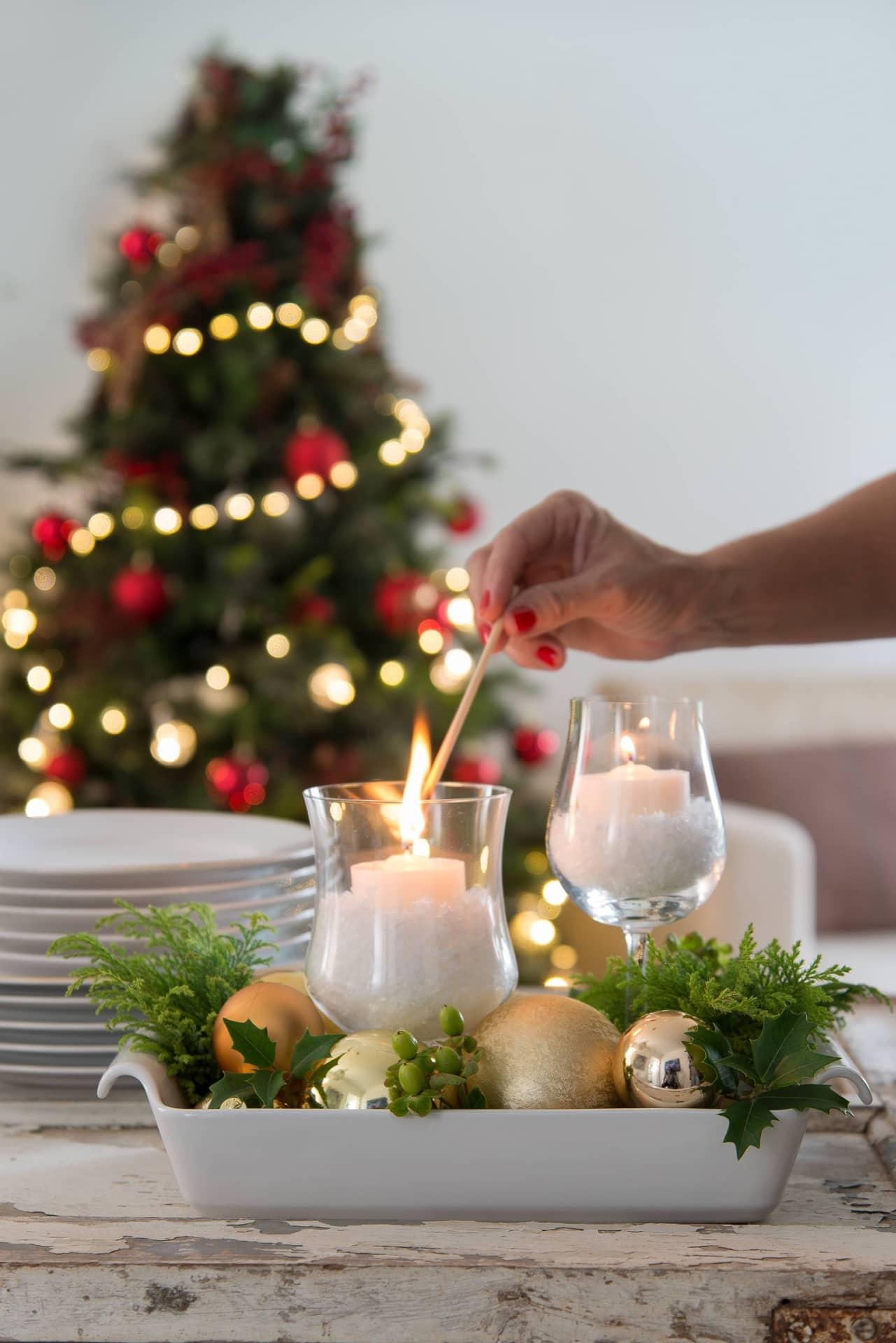 Imagem: Para completar o centro de mesa, use uma travessa refratária como bandeja. Coloque bolas de Natal em vários tons de dourado, brilhantes e foscas. Os copos viram castiçais com velas apoiadas em neve artificial da @emporiodasfloresoficial.Foto: Cacá Bratke.
