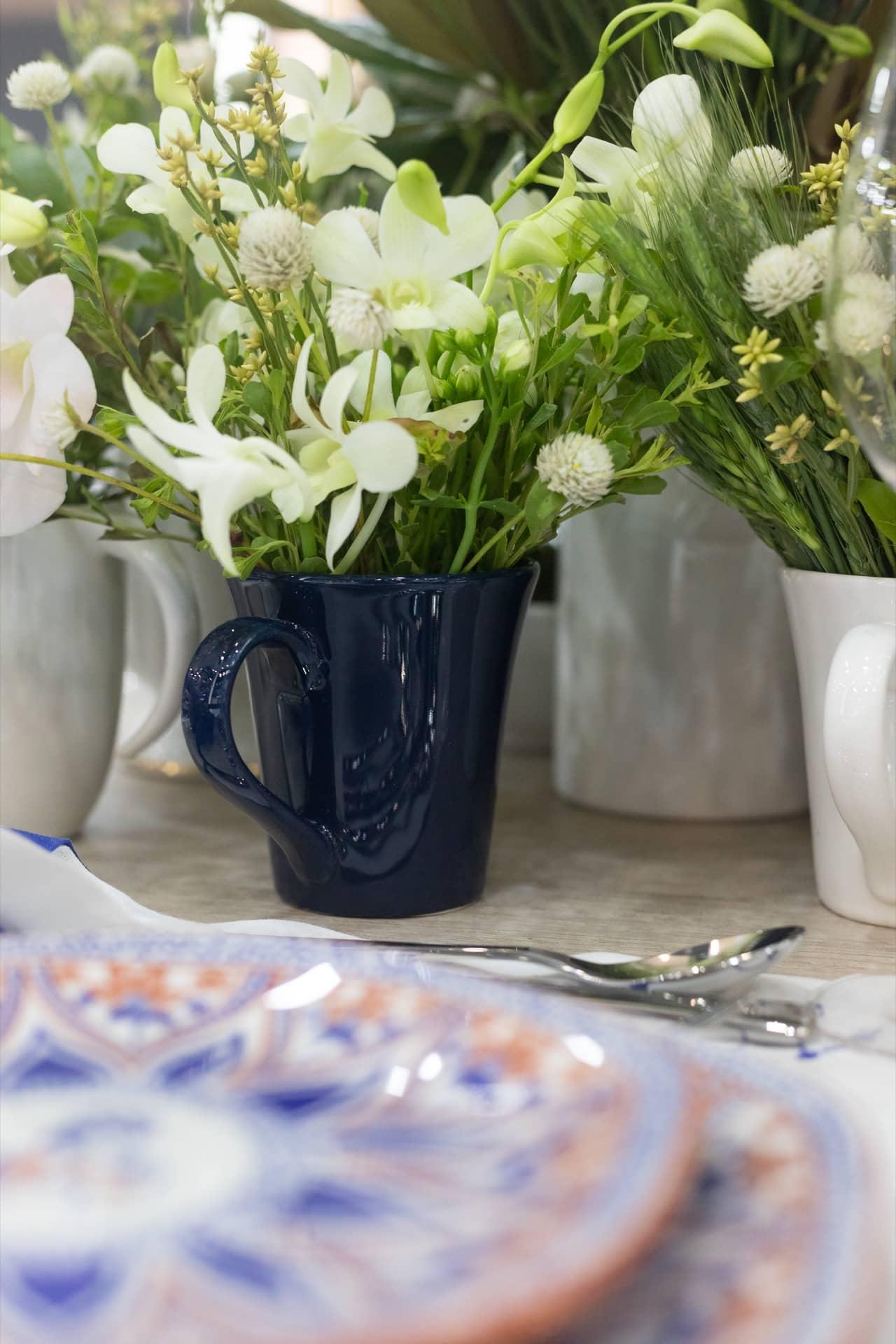 Imagem: No centro da mesa, o arranjo floral foi feito em jarras, bowls, açucareiros e canecas. Como as alturas são variadas, o efeito é especial. Quer mais dicas de como inovar nos arranjos de flores para a mesa? O Puxe uma Cadeira tem dicas especiais nesse post aqui. Foto: Carolina Prieto.