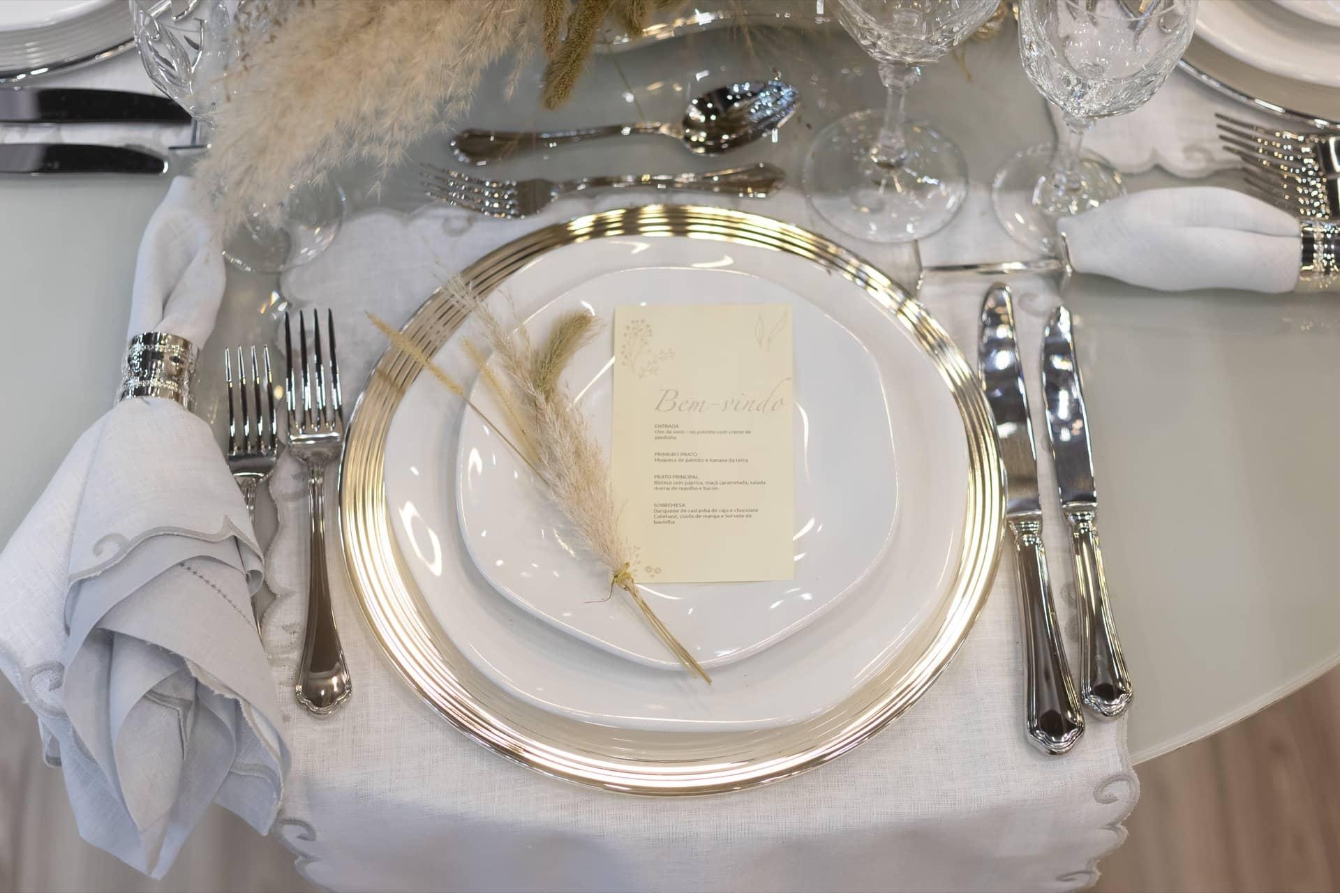 Imagem: Na mesa posta para um jantar elegante, pratos da linha Ryo White, da Oxford Porcelanas, fazem parceria com sousplats, argolas de guardanapo e talheres de prata da St. James. Foto: Carolina Prieto.
