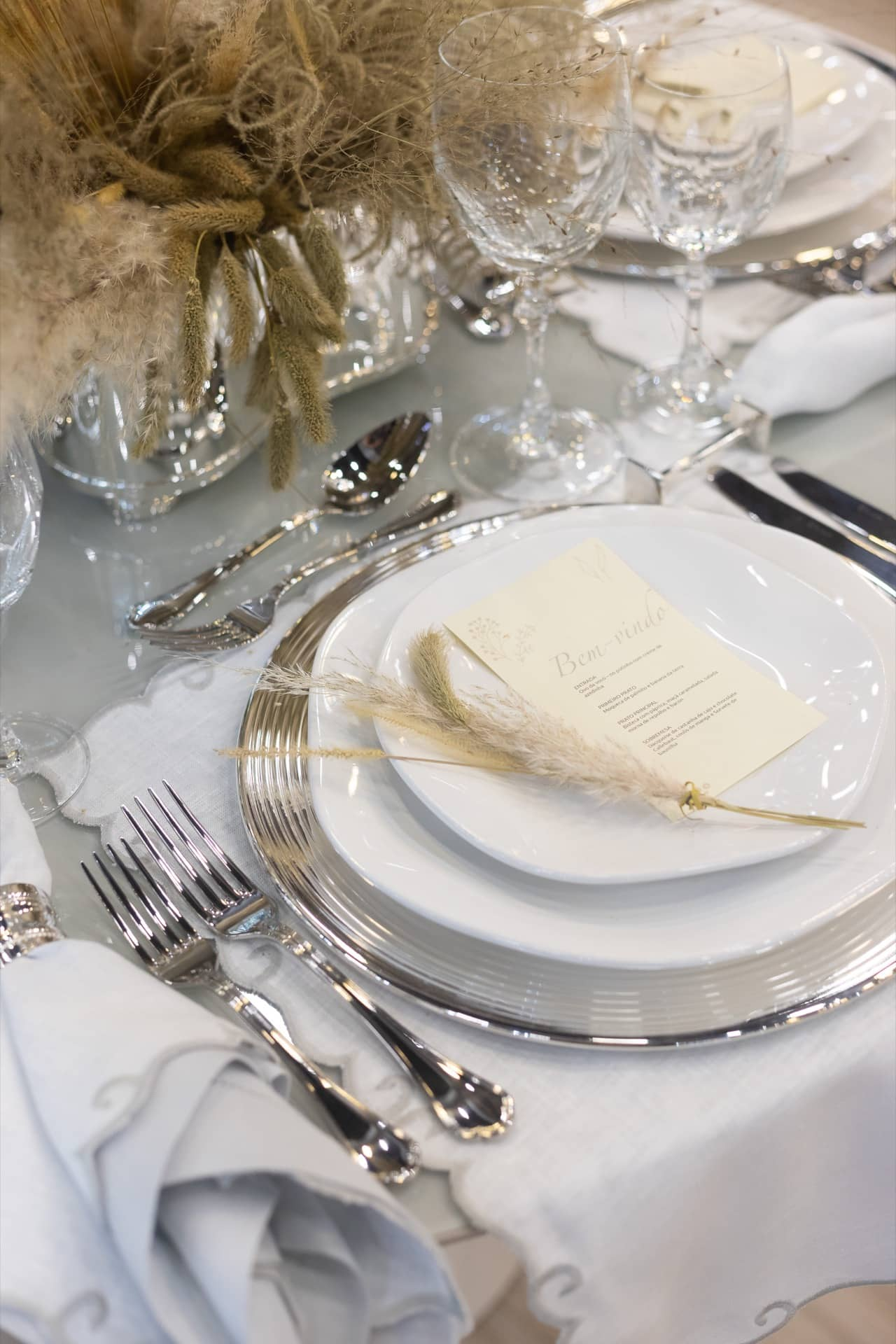 Imagem: O menu do jantar é impresso em papel de qualidade e colocado sobre o prato da entrada. Um ramo de trigo arremata o visual. Foto: Carolina Prieto.