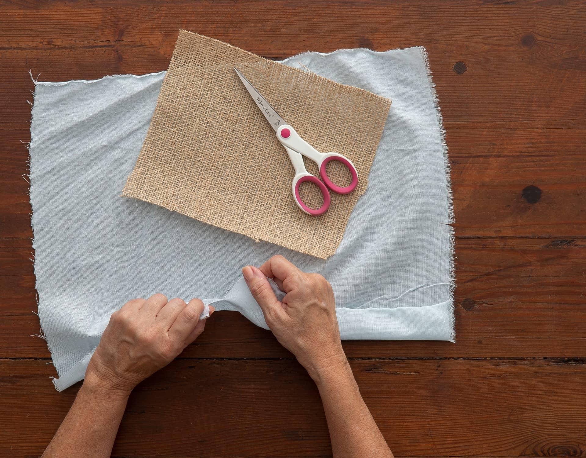 Imagem: Passo 2: corte um quadrado um pouco menor do tecido. Dica: para que ele tenha um aspecto desfiado, faça um pequeno corte no tecido com a tesoura, e rasgue. Foto: Cacá Bratke.
