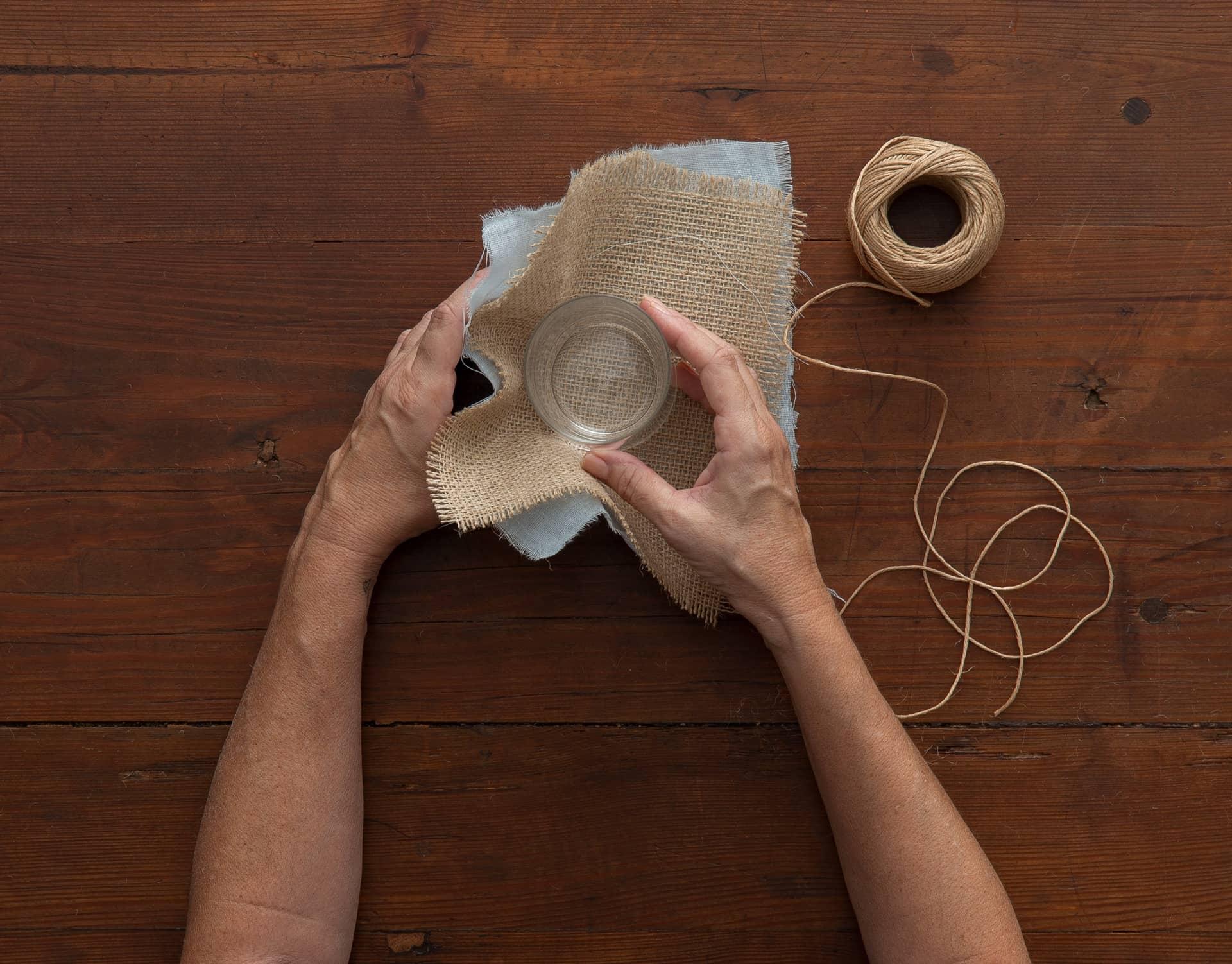 Imagem: Passo 4: envolva o copo com os dois tecidos. O algodão vai por fora e a juta, por dentro. Foto: Cacá Bratke.