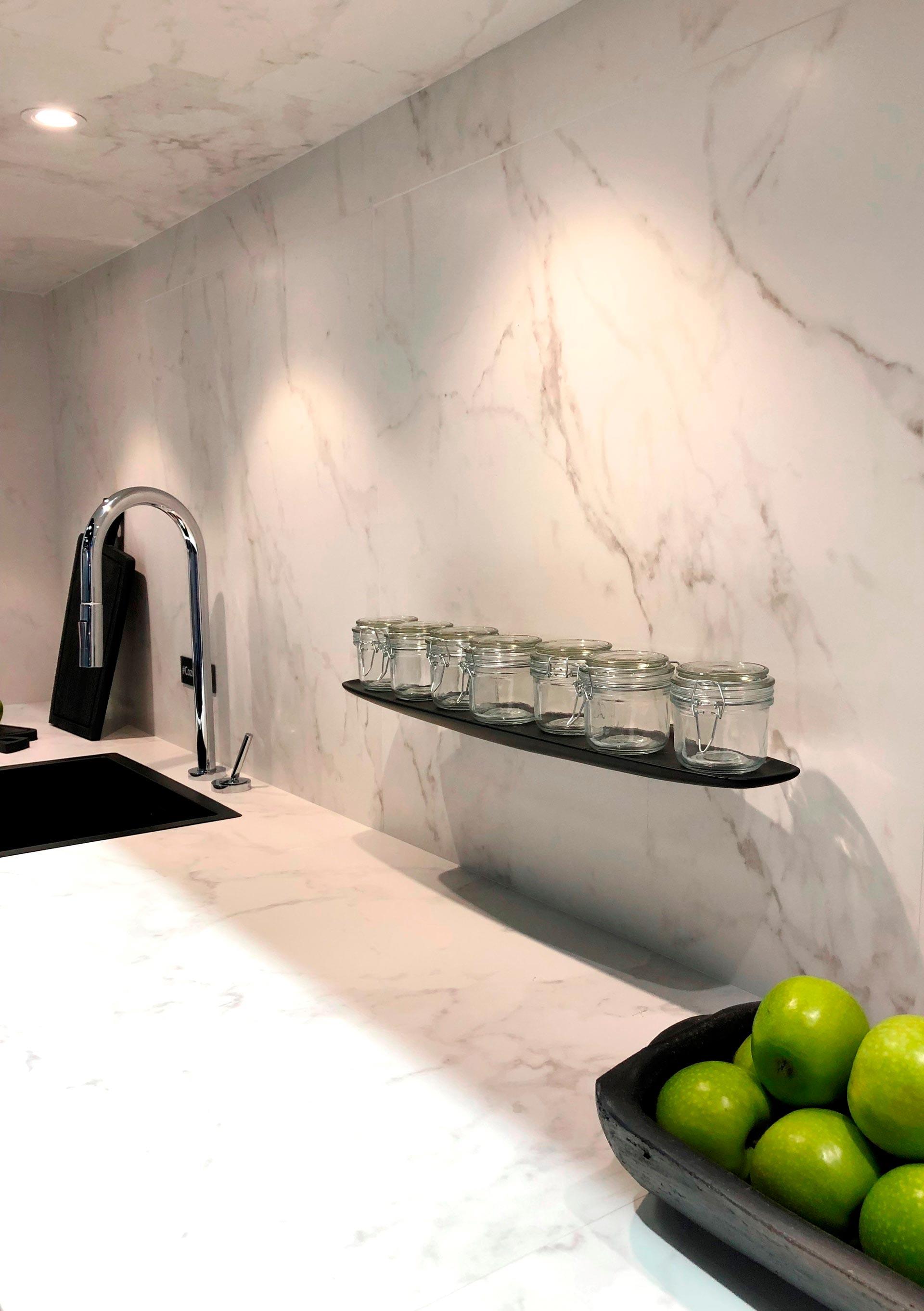 Imagem: No estande da Deca: uma cozinha minimalista e inteira marmorizada - bancada e revestimento da parede. Foto: Arquiteca Projetos.