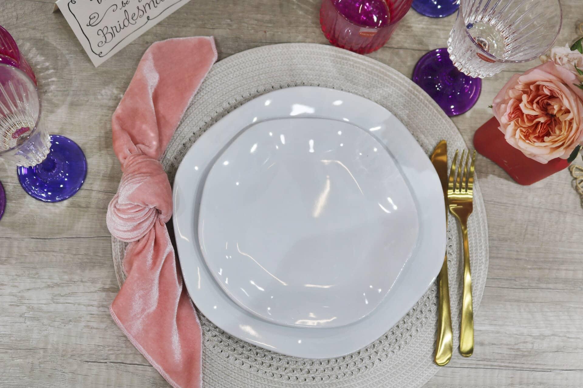 Imagem: O lugar da noiva é sinalizado pelo jogo americano branco. As louças são da coleção Ryo White da linha Oxford Porcelanas, e as taças, da Biona. Foto: Lorena Baroni Bosio.