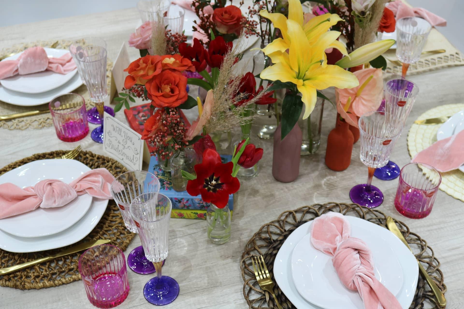 Imagem: Flores sortidas, e taças de várias cores, criam o clima festivo da mesa. A louça branca, Ryo White da linha Oxford Porcelanas, equilibra o conjunto com suas formas sinuosas. Foto: Lorena Baroni Bosio.