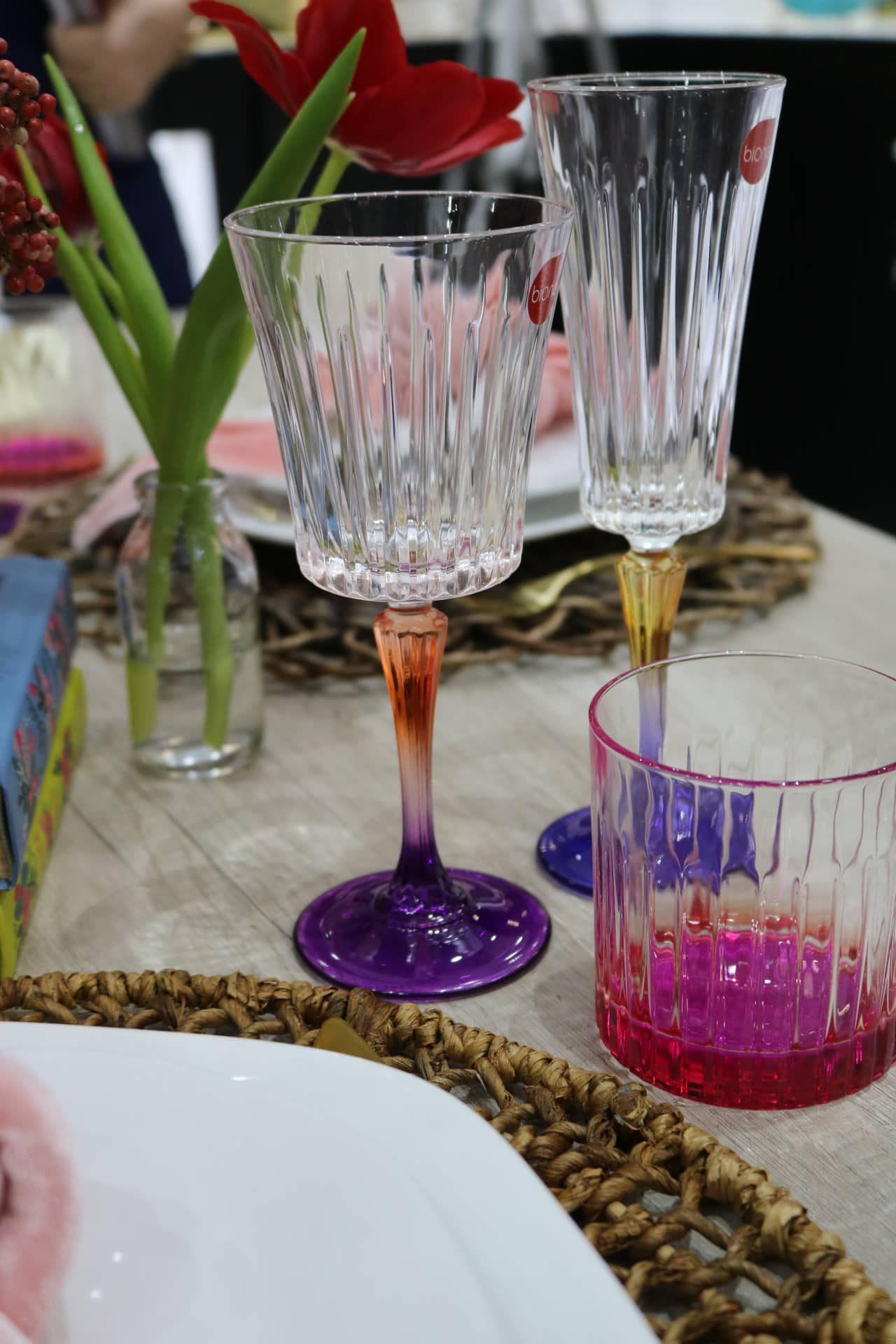 Imagem: Com tonalidades intensas e design atual, as taças para vinho e espumante, assim como o copo para água, são da Biona e podem ser encontrados em lojas de todo país. Foto: Lorena Baroni Bosio.