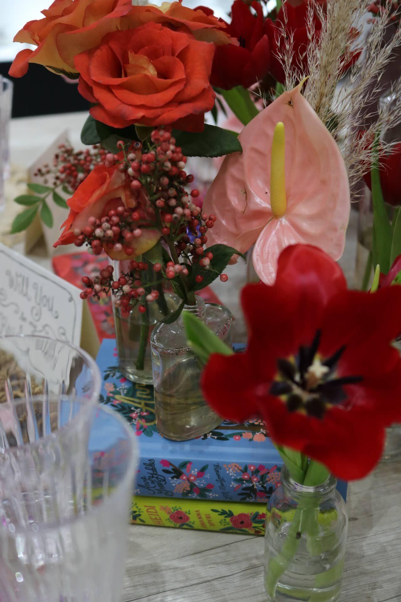 Imagem: No centro da mesa, use alguns livros como apoio para os vasos de flores. Assim, os arranjos ficam com alturas variadas. Foto: Lorena Baroni Bosio.
