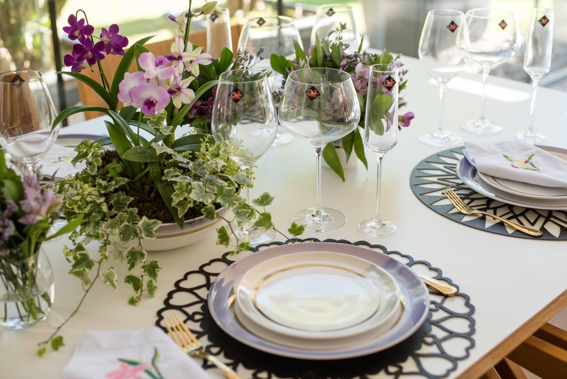 Imagem: No centro da mesa, os arranjos de flores incluem orquídeas, astromélias, musgo e hera variegata. O maior deles foi feito dentro de uma travessa de louça da coleção Coup Glam da Oxford Porcelanas. As taças de cristal são da Oxford Alumina Crystal. Foto: Karla Rudnick.