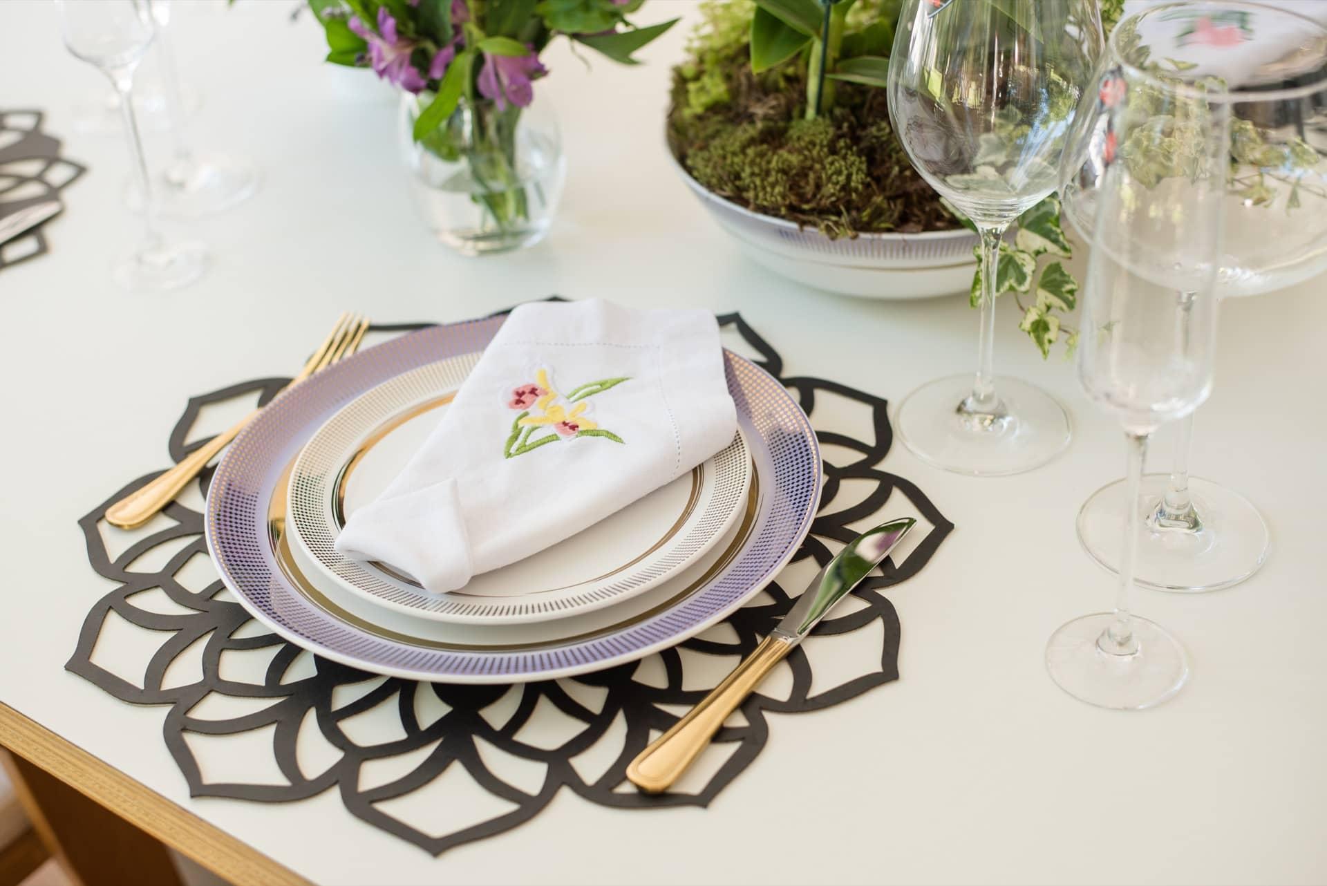 Imagem: As flores que enfeitam a mesa aparecem também nos guardanapos de linho bordados do Ateliê da Mesa. Foto: Karla Rudnick.