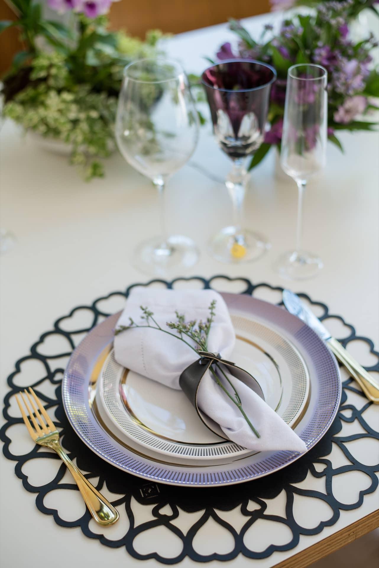 Imagem: Repare na harmonia entre os tons de rosa, lilás e vinho, presentes na porcelana, na taça de cristal overlay e nos arranjos de flores. Foto: Karla Rudnick.