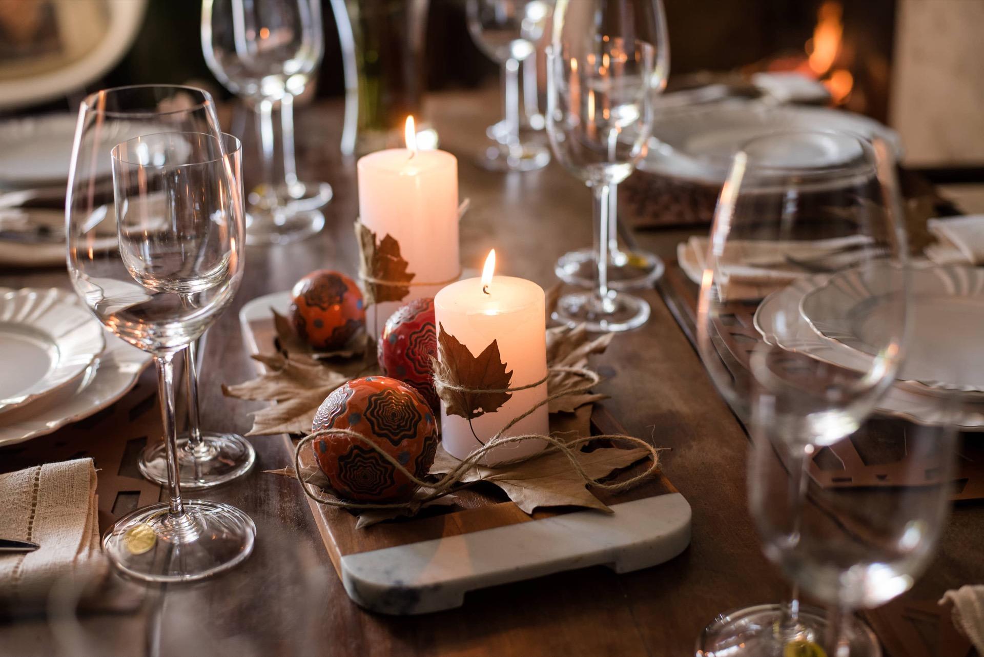 Imagem: No centro da mesa, uma tábua de madeira e mármore, da Oxford (à venda em lojas físicas de todo Brasil), acomoda o arranjo com bolas decoradas, velas e folhas secas.Foto: Karla Rudnick