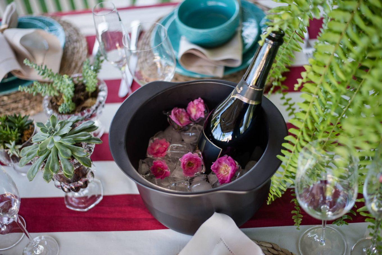 Imagem: A champanheira é uma panela de cerâmica Linea Nanquim da Oxford Cookware. E para deixar a mesa ainda mais charmosa, coloque botões de mini rosas junto com os cubos de gelo. As suculentas ficam dentro de taças de vidro. Foto: Karla Rudnick