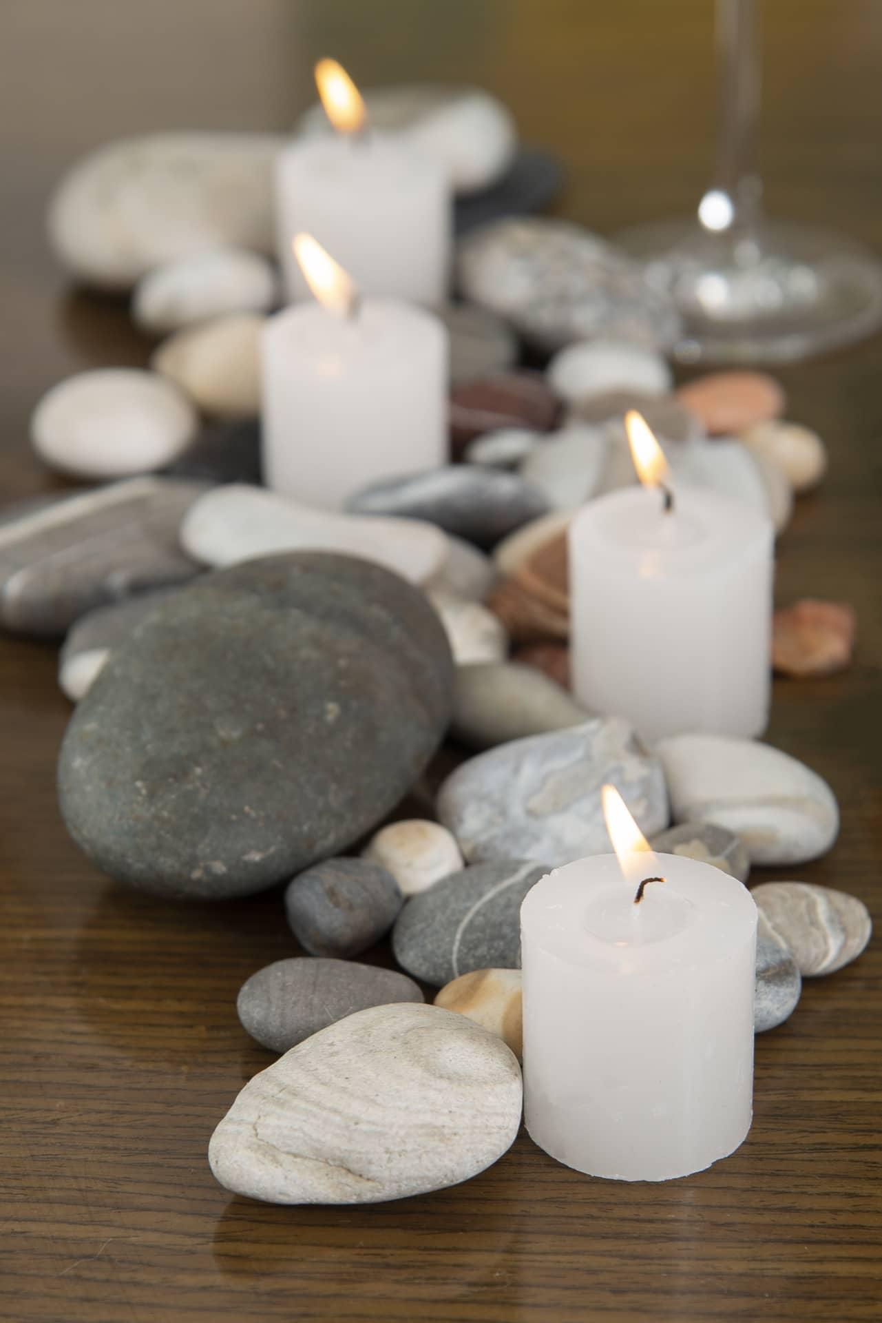 Imagem: Para compor o centro de mesa, espalhe seixos de vários tamanhos, em tons de cinza, e algumas velas brancas, largas e baixas. Fotos: Cacá Bratke