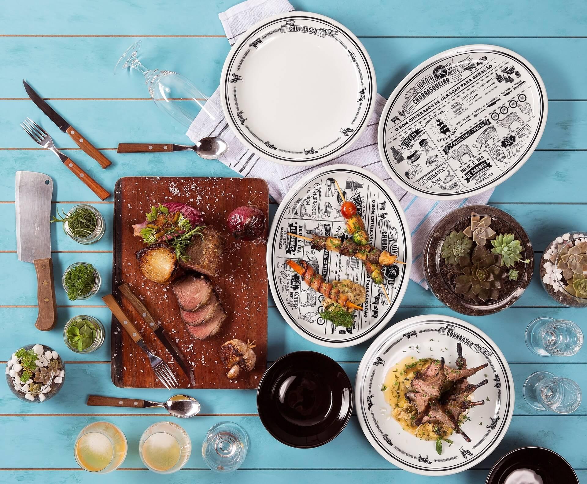 Imagem: Mesa de piquenique colorida com churrasco servido. Conjunto Jornal do Churrasqueiro, da Oxford.