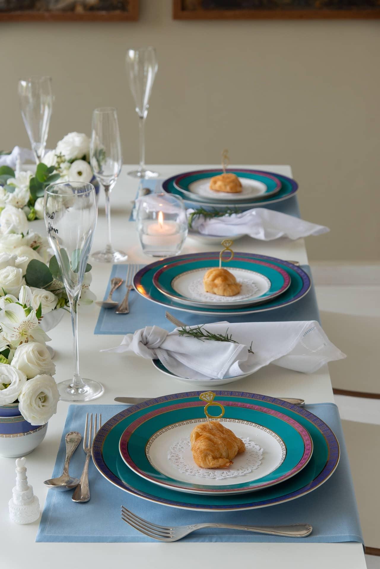 Imagem: No jantar para os padrinhos, o aparelho de jantar, com cores inspiradas em pedras preciosas brasileiras, contracena com jogos americanos azuis, guardanapos brancos e taças de espumante para festejar a ocasião.Velas e flores brancas são coadjuvantes indispensáveis. Foto: Cacá Bratke