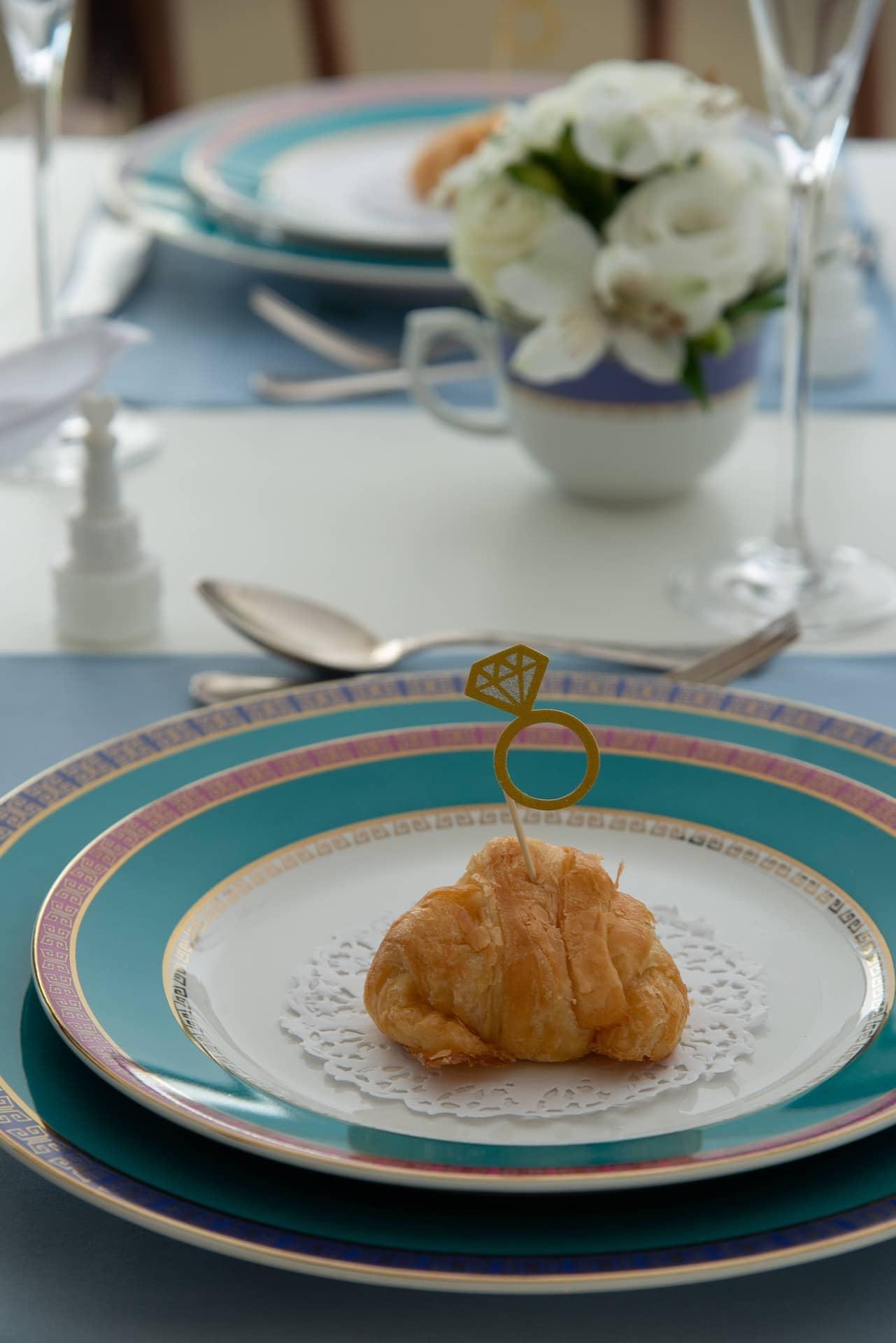 Imagem: Sobre cada prato de sobremesa, da coleçãoFlamingo Joia Brasileira da Oxford Porcelanas, vai um mini croissant enfeitado com um anel de noivado estilizado, da Rica Festa. Embaixo do pãozinho, uma toalhinha de papel rendado dá acabamento ao mimo. Foto: Cacá Bratke