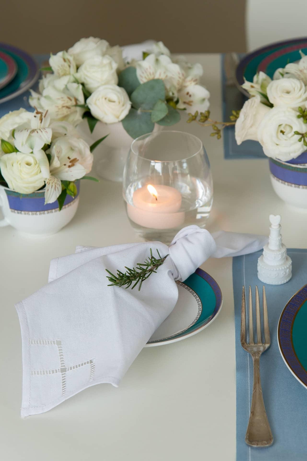 Imagem: O guardanapo de tecido ganha um toque especial, com um nó na ponta e um ramo de alecrim. Ele fica apoiado sobre um pires do mesmo jogo de jantar da Oxford Porcelanas. Foto: Cacá Bratke