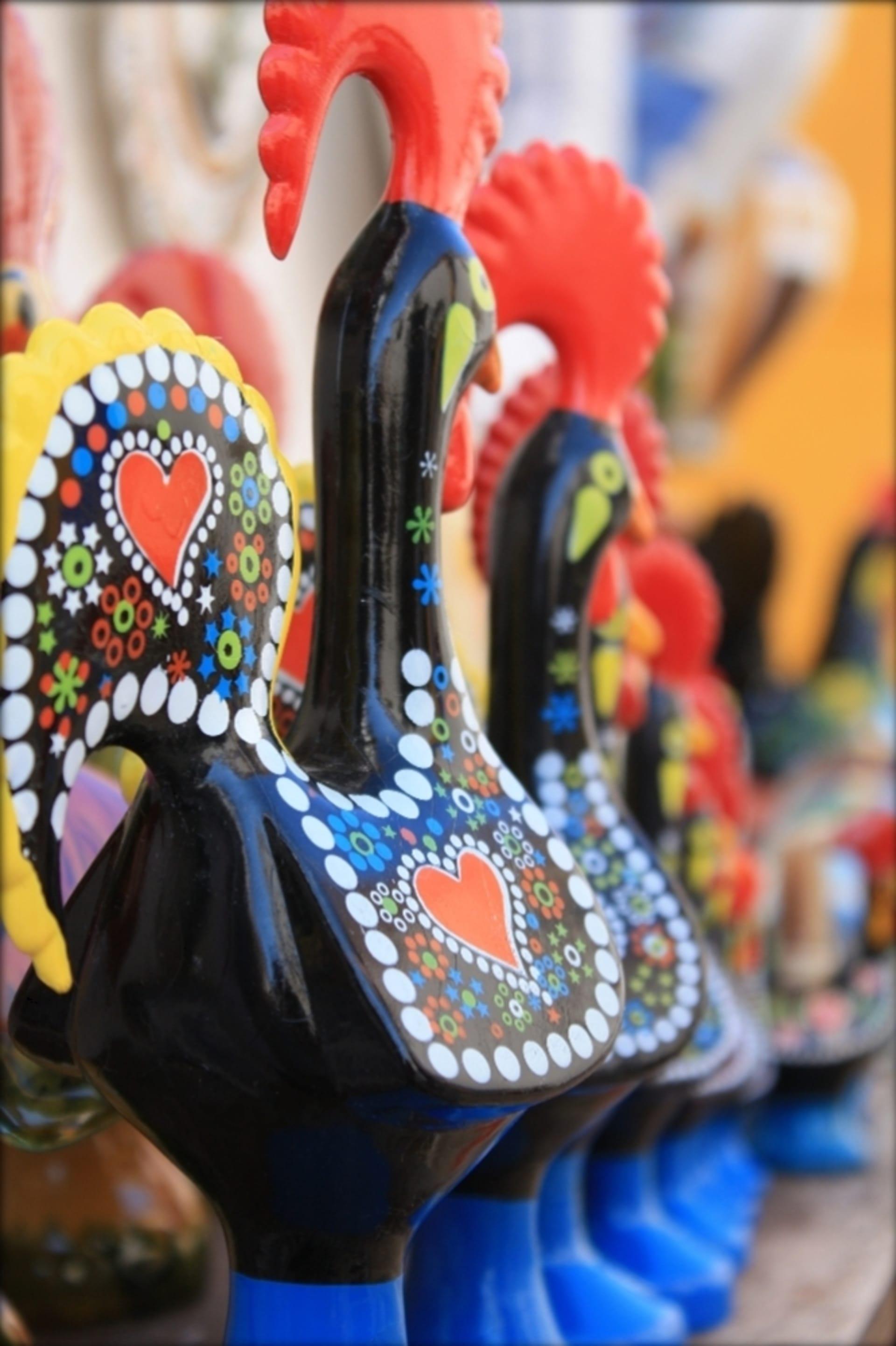 Imagem: Souvenir galo de Barcelos com pintura artesanal. As cores predominantes geralmente são preto, vermelho, amarelo e azul.