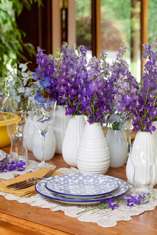 Imagem: Muitas flores na mesa! E já que a cor forte está nelas, nada melhor do que apostar em vasos mais discretos. Foto: Julia Ribeiro.