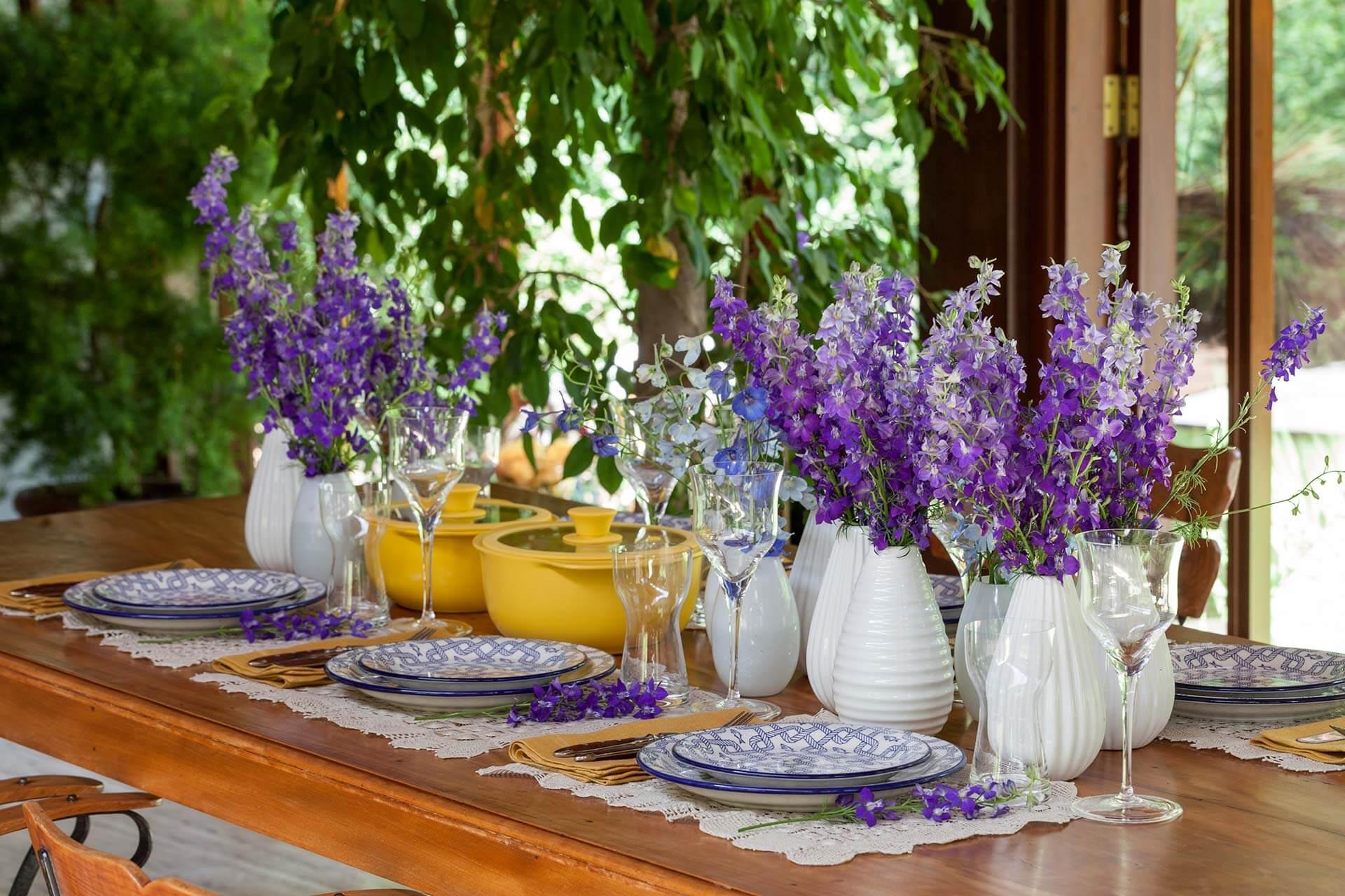 Imagem: O contraste entre cores fortes chama a atenção nessa mesa para almoço. Tons de azul, amarelo e roxo estão em perfeita harmonia na composição. Foto: Julia Ribeiro.