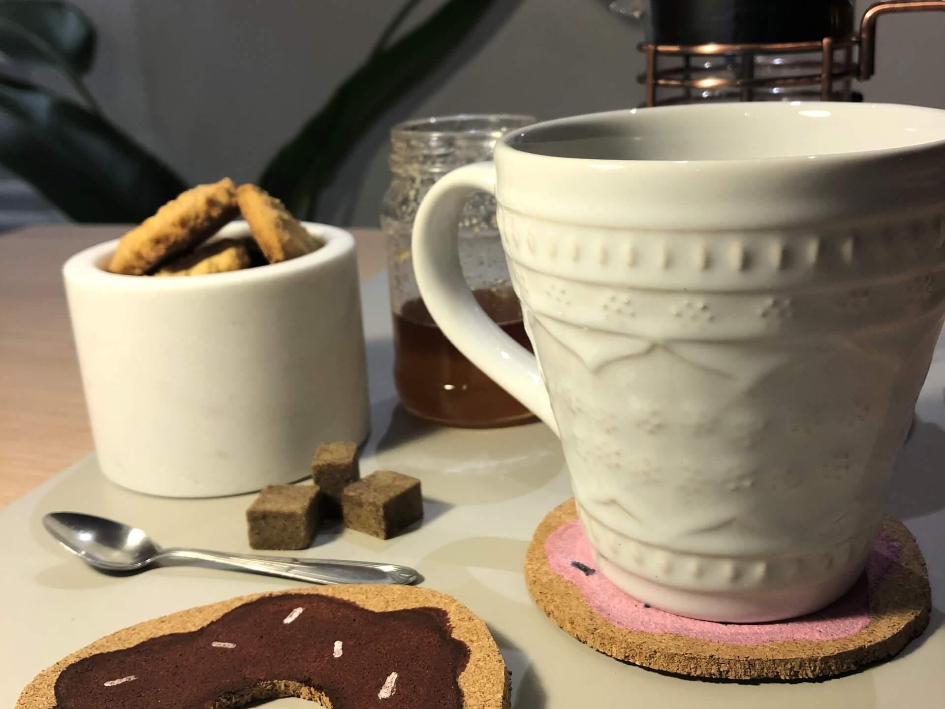 Imagem: Sobre as bolachas está a caneca Oxford Serena White que você pode encontrar aqui. Ao fundo, estão a cafeteira Cafeteira francesa - disponível aqui - e o marmorizado Oxford disponível em nossas revendas. Foto: Arquiteca Projetos.