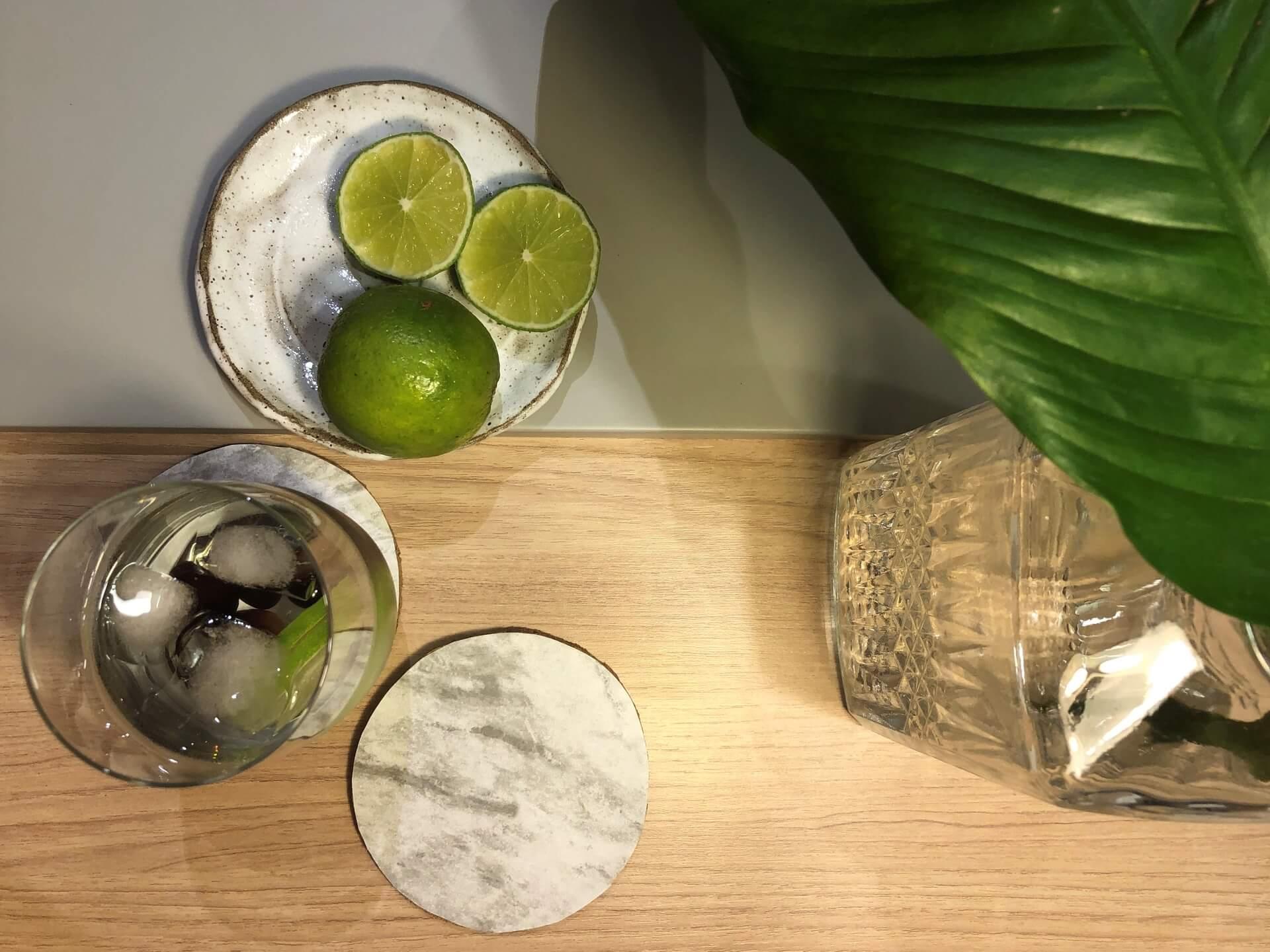 Imagem: Mesa tropical e minimalista com as bolachas de cortiça marmorizadas e os copos Oxford Touch Long Drink. Foto: Arquiteca Projetos.