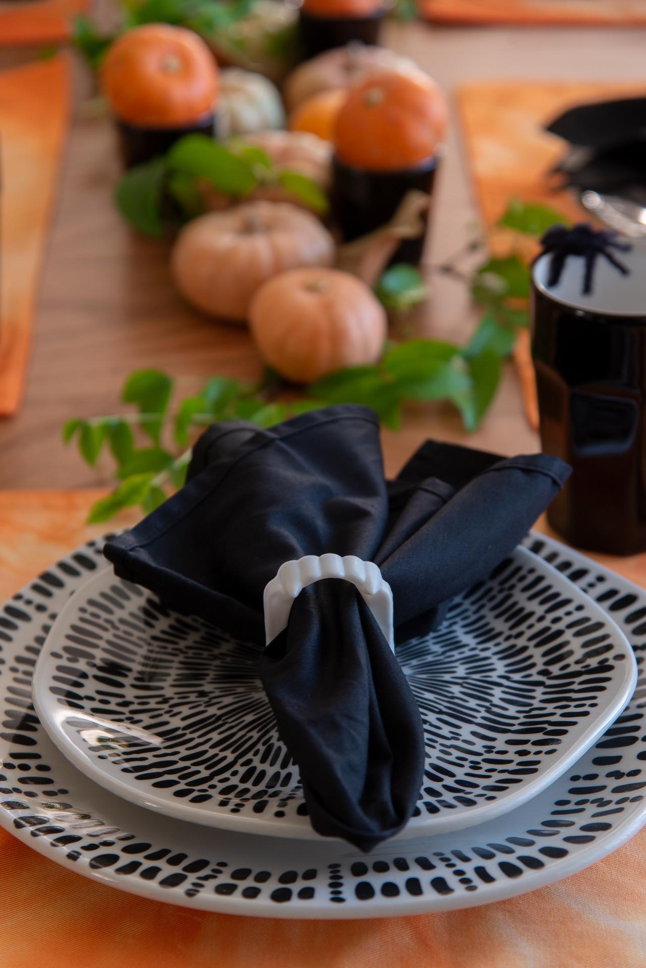 Imagem: O aparelho de jantar, que apresenta formas sinuosas e pinceladas com aspecto manual, é da coleção Ryo Ink da Oxford. O anel de guardanapo é uma dentadura de vampiro, que você encontra facilmente em casas de material para festas. Foto: Cacá Bratke
