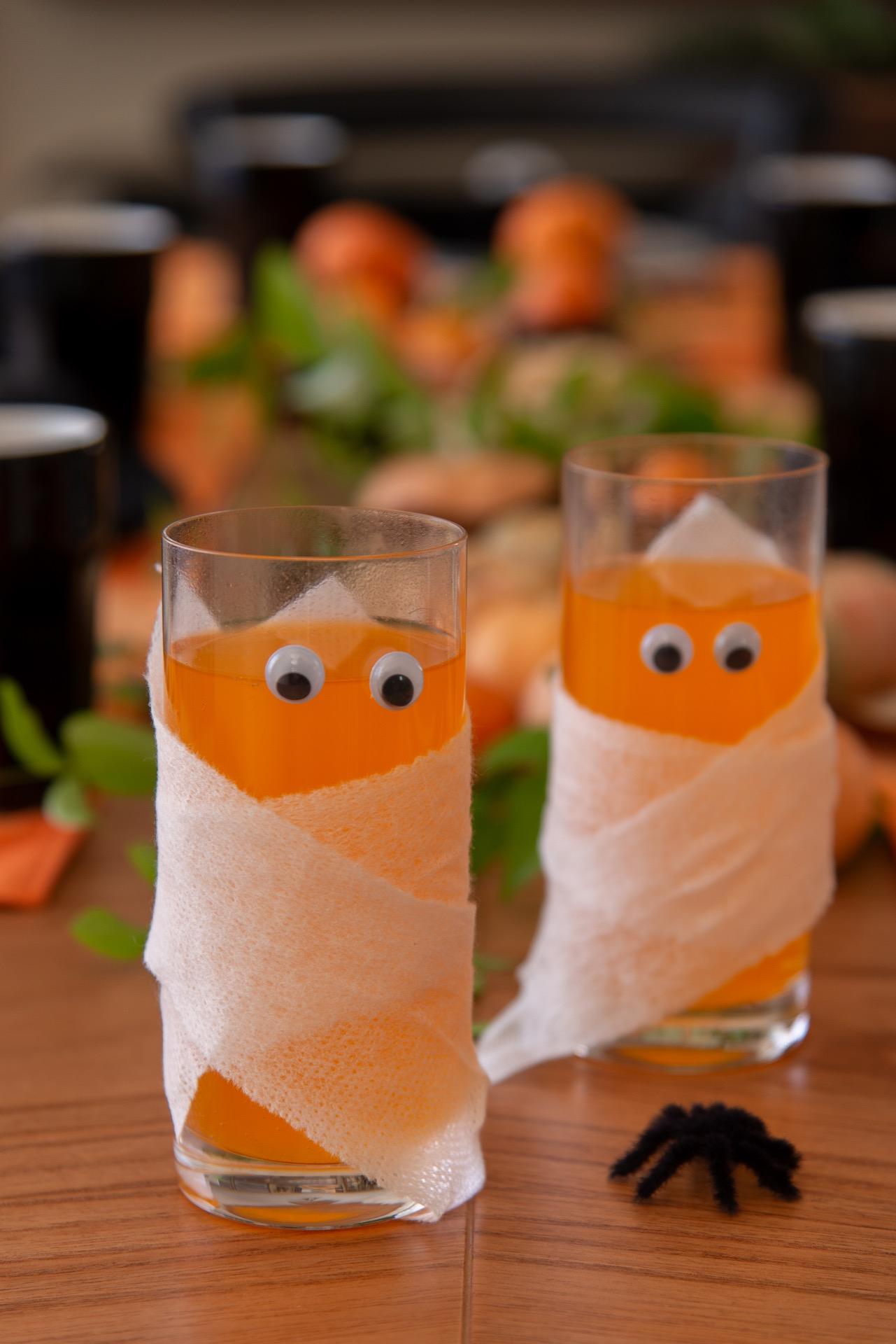 Imagem: Para que os convidados entrem no clima, sirva refrigerante de laranja em copos decorados como múmias. Basta enrolar uma gaze em volta do copo e colar olhinhos. Foto: Cacá Bratke