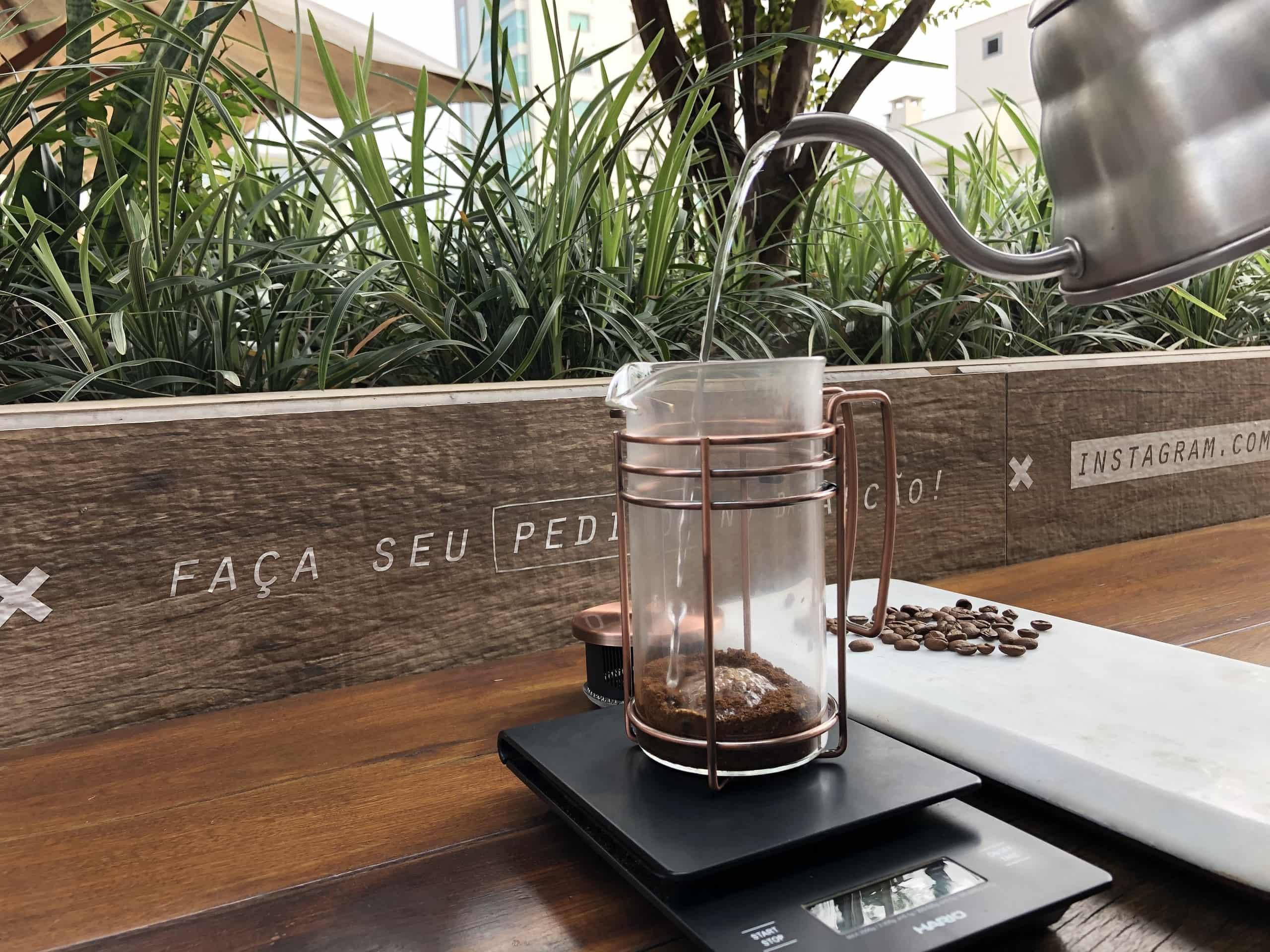 Imagem: Café especial filtrado na Prensa Francesa. A primeira queda, assim como no método Hario V60, serve somente para umedecer o pó de café. Garanta que você tenha molhado todo o pó e aguarde aproximadamente 30 segundos até a segunda queda. Foto: Arquiteca Projetos Afetivos.