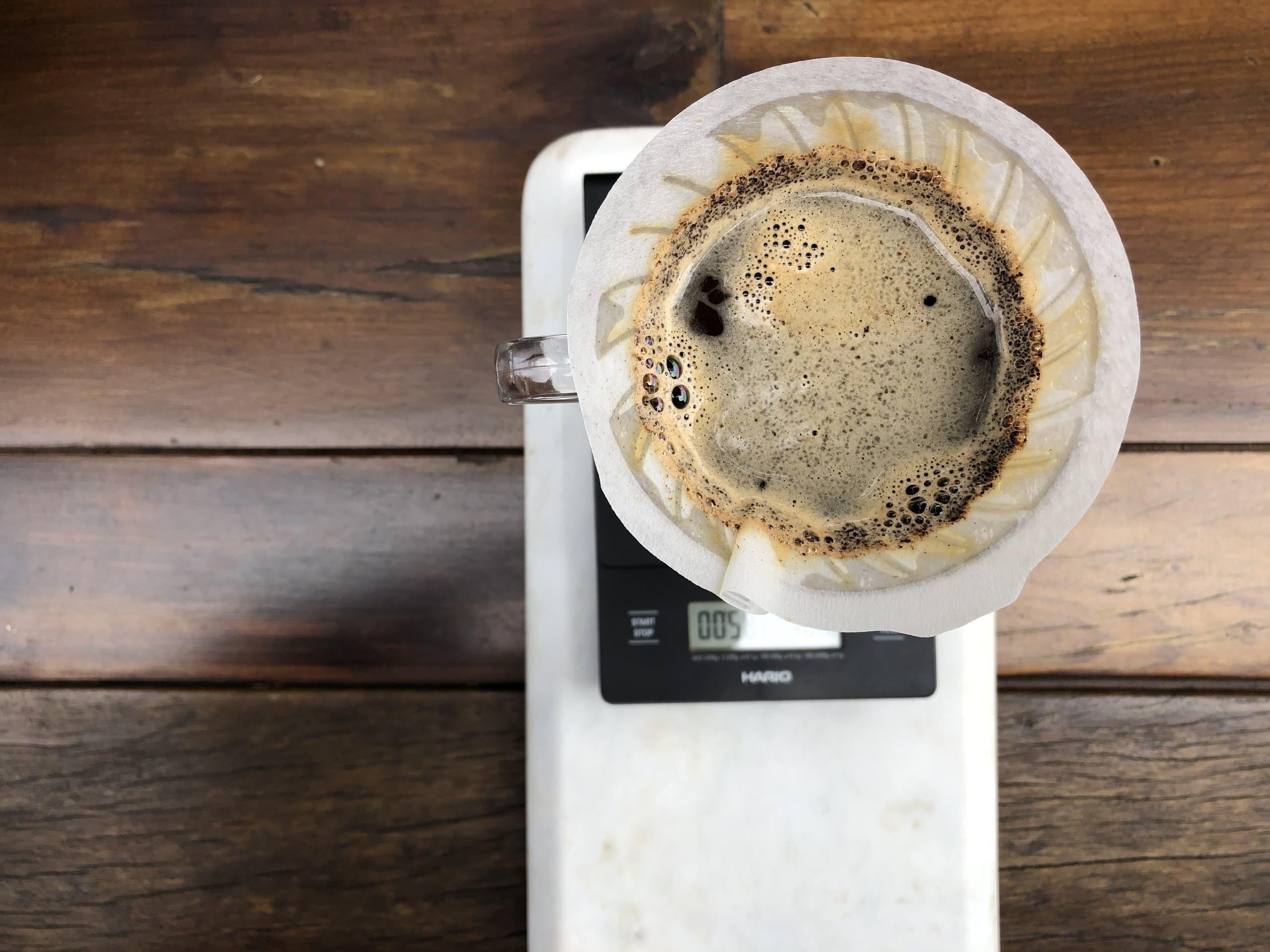 Imagem: Café especial filtrado na Hario V60. Nas próximas quedas mire bem no meio do coador - isso evita que você destrua a parede de pó que foi formada em volta do filtro. Foto: Arquiteca Projetos Afetivos.