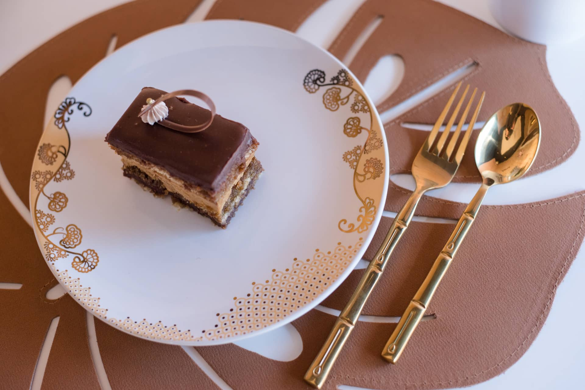 Imagem: O jogo americano de couro e os talheres dourados, complementam o prato da coleção Coup Golden da Oxford. O doce, com massa de amêndoas e recheio de creme de café e chocolate, é da Manu Rosa Bakery. Foto: Karla Rudnick