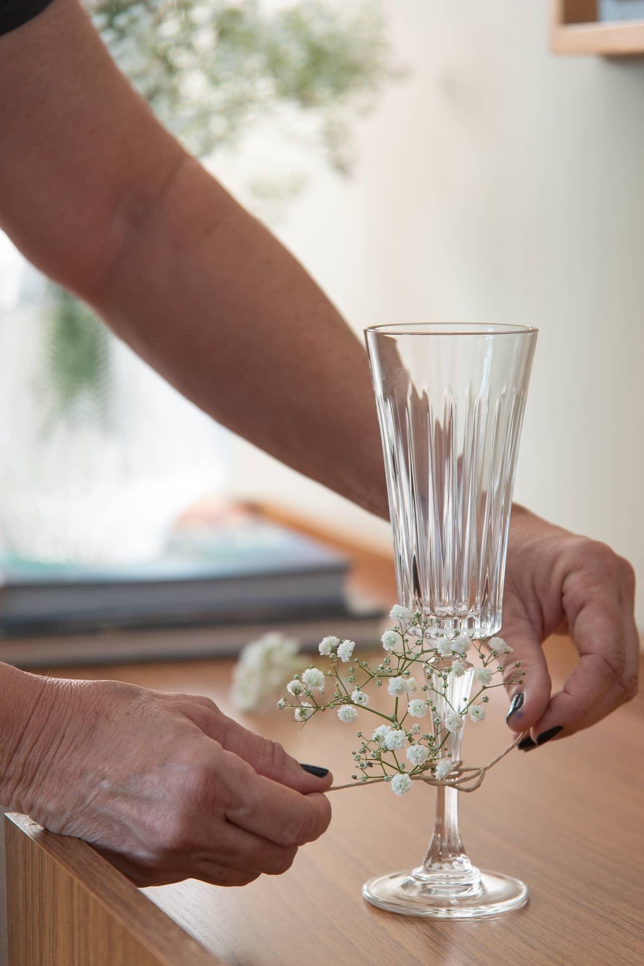 Imagem: Passo 2: corte o fio de rami com a tesoura e amarre frouxamente no pé da taça. Coloque as flores por dentro do barbante e aperte o nó para prendê-las. Foto: Cacá Bratke
