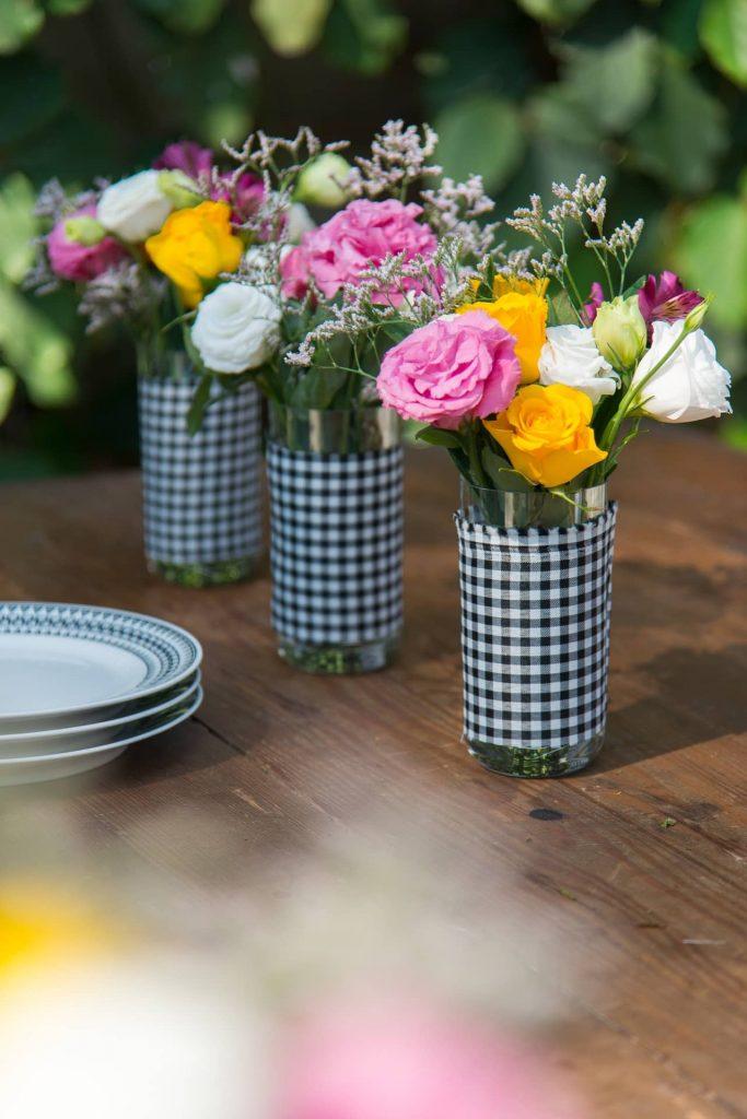 """Imagem: Transforme copos de long drink em vasos decorativos. É só cortar um pedaço de tecido e colar com fita dupla-face. Para mais detalhes, veja o <a href=""""https://puxeumacadeira.com.br/diy-vaso-de-flor-decorado-com-tecido/"""">post com DIY</a>. Foto: Cacá Bratke."""