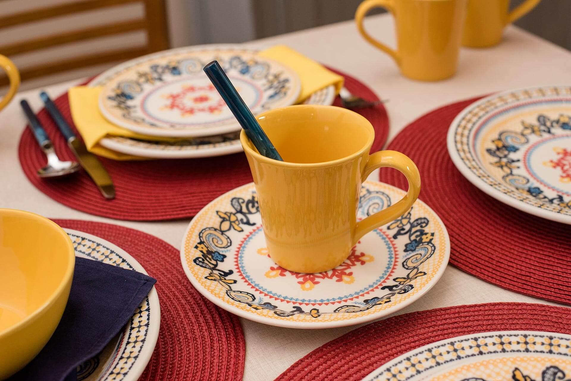 Imagem: Em tons de amarelo, azul e escarlate, a coleção Floreal La Pollera, da Oxford, fica ainda mais bonita sobre jogos americanos vermelhos. Os guardanapos de tecido, em amarelo ou azul índigo, acrescentam mais um ponto de cor, Foto: Karla Rudnick