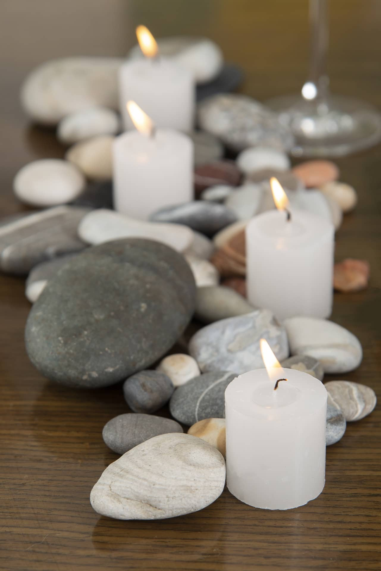 Imagem: Entre as ideias criativas para a mesa posta, esta é uma das mais simples e originais. Disponha seixos, de diferentes tamanhos e cores, junto a velas brancas, grossas e baixas. Foto: Cacá Bratke.