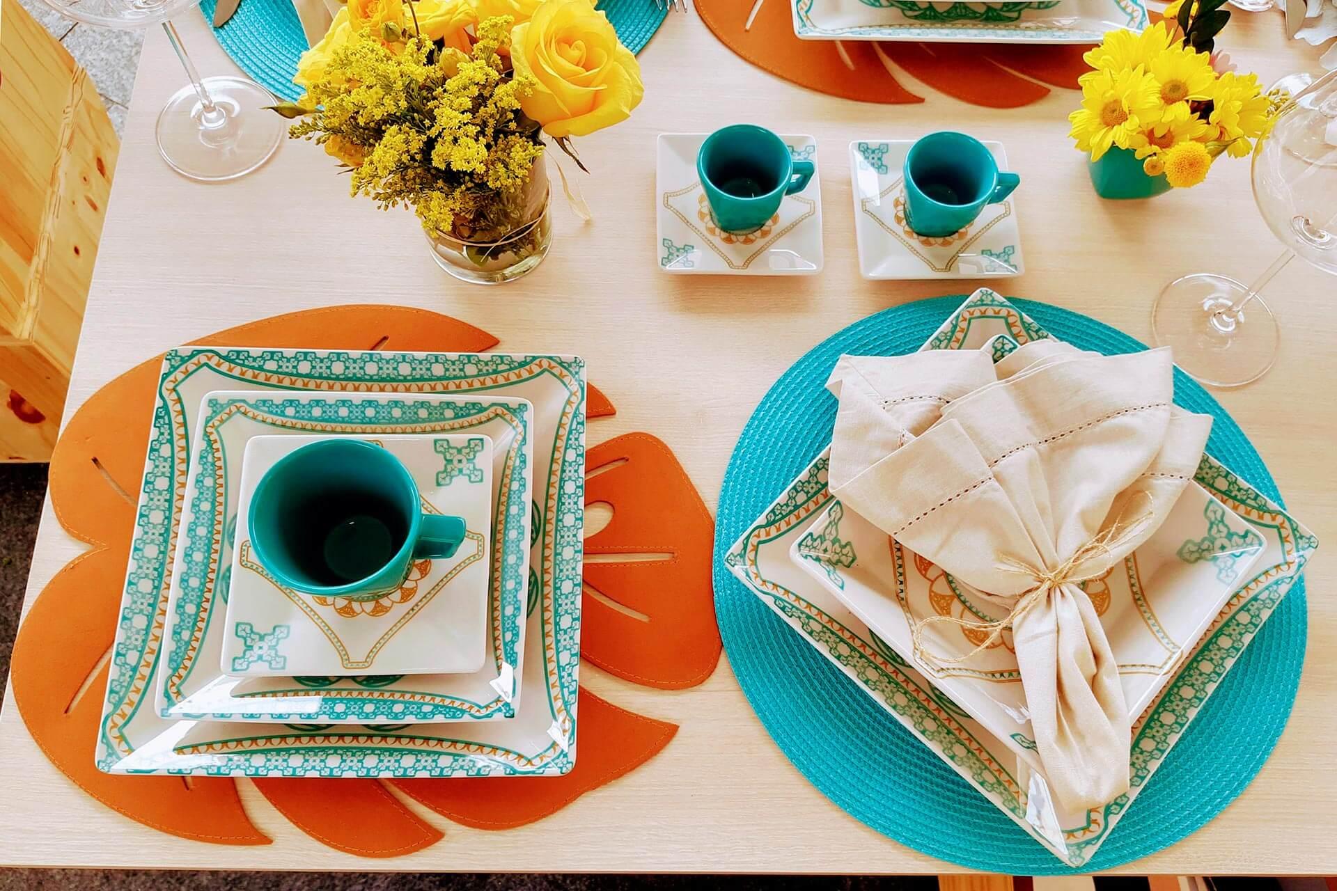 Imagem: O conjunto de porcelanas Quartier Domo, da Oxford Porcelanas, ganha destaque sobre jogos americanos circulares e com formato de folha. Repare que são os tons de laranja e turquesa que harmonizam tudo.