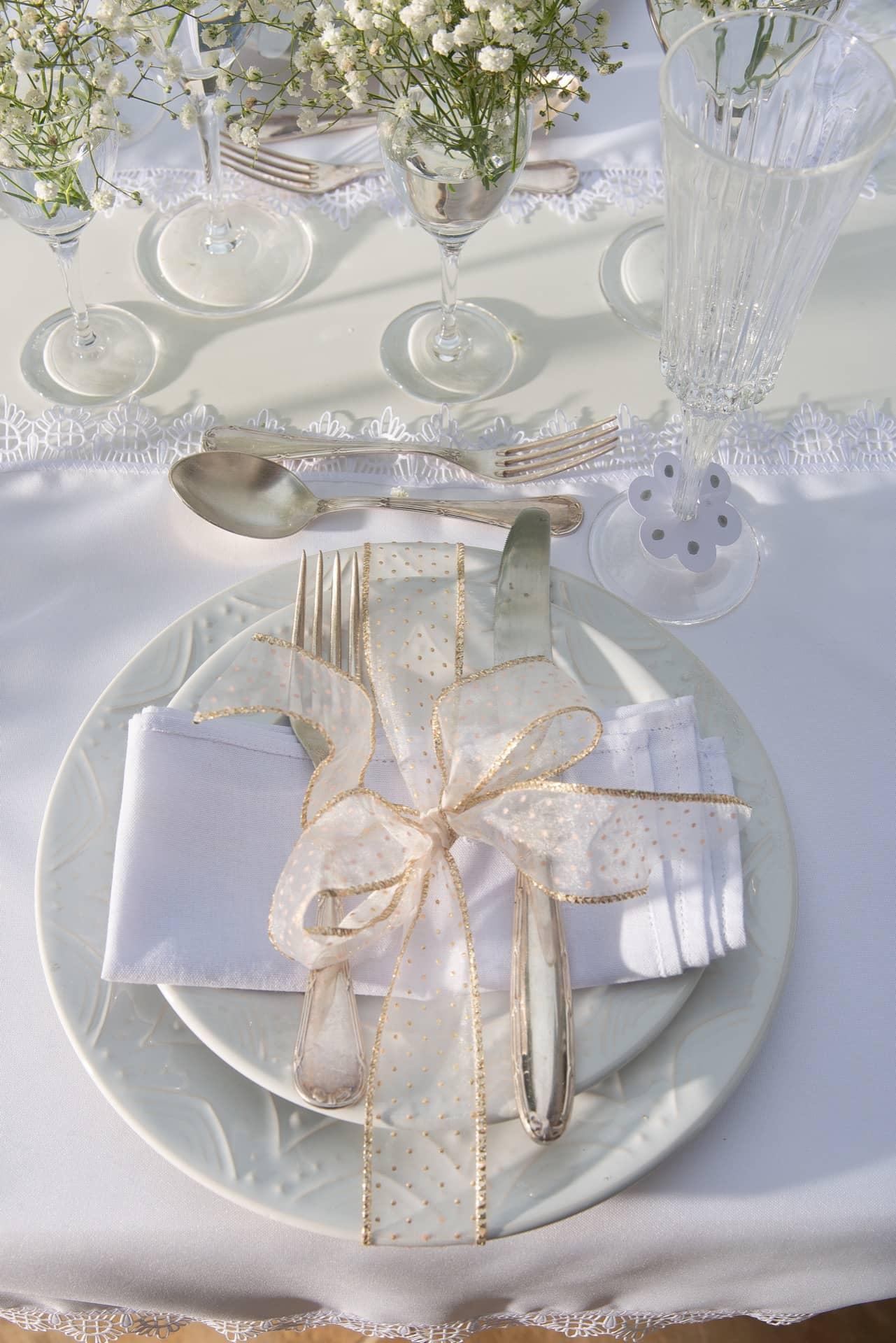 Imagem: Os pratos Serena White, da Oxford, aparecem embrulhados em fitas transparentes com detalhes dourados. Como a mesa está ao ar livre, os talheres ficam sobre os guardanapos para que estes não voem. Foto: Cacá Bratke