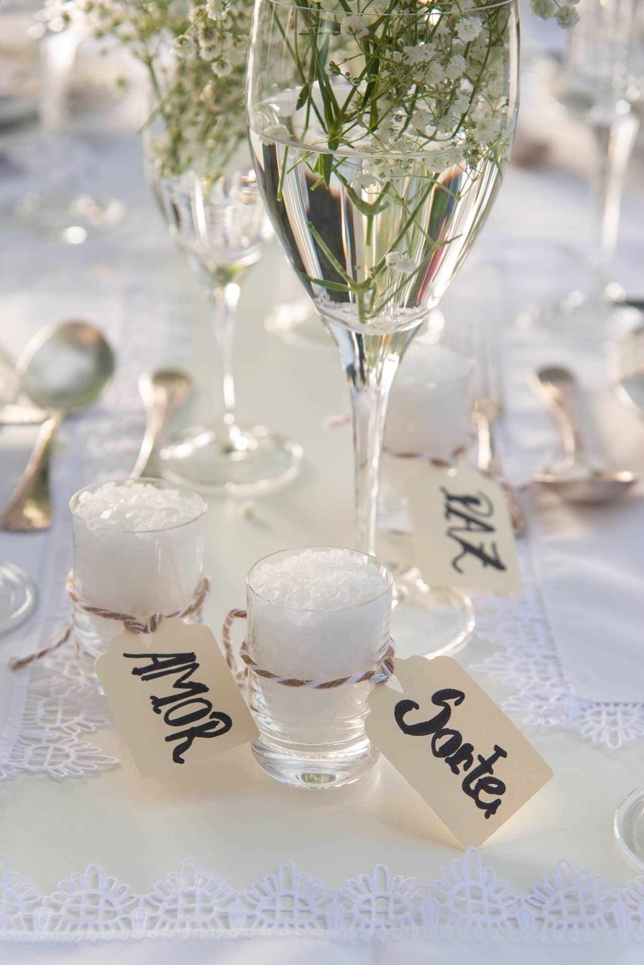 Imagem: Copinhos de cachaça com sal grosso e etiquetas com votos de paz, amor e sorte, atraem boas energias para a mesa posta de Ano Novo. Foto: Cacá Bratke